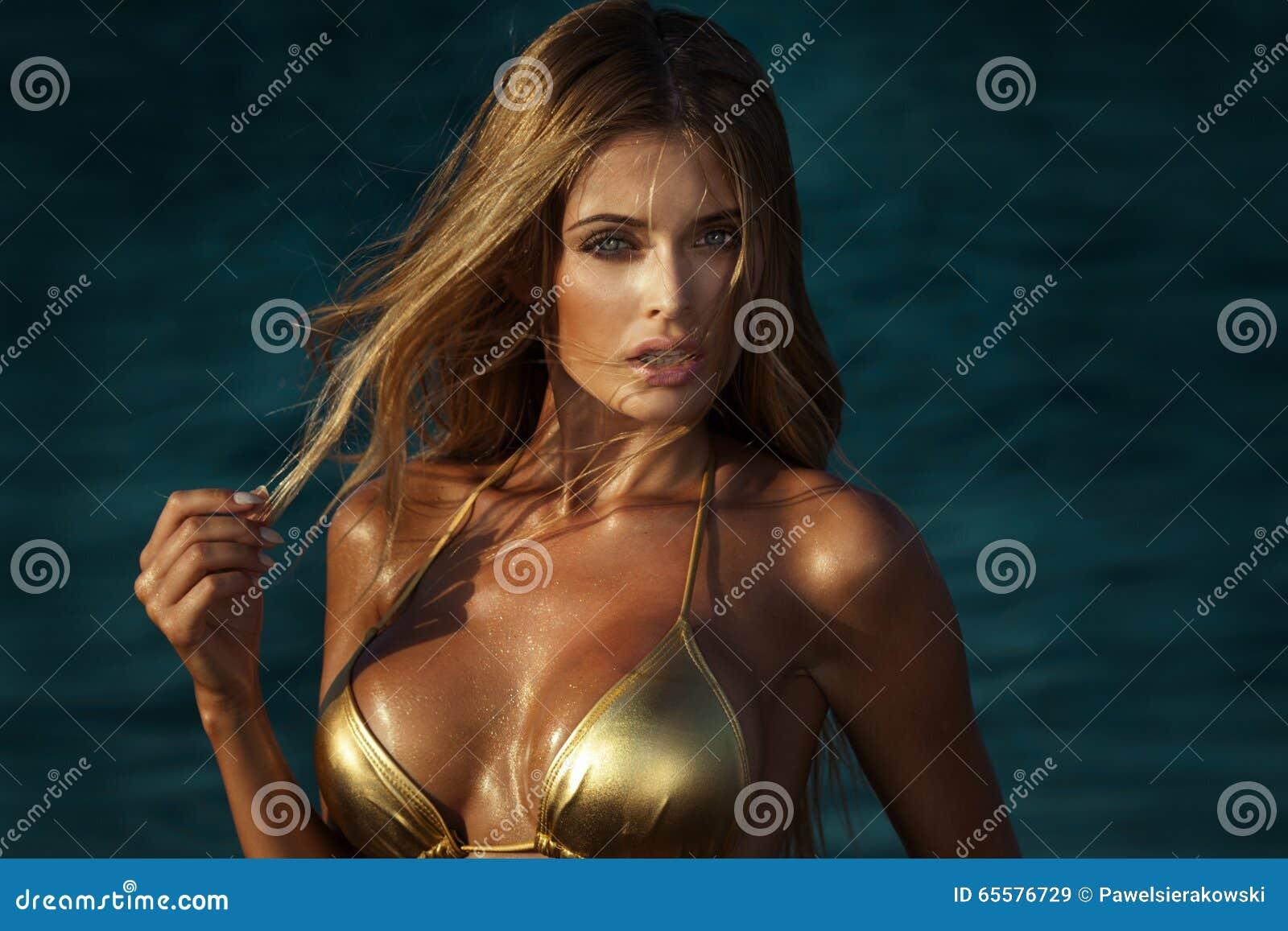 Retrato da mulher loura no biquini do ouro