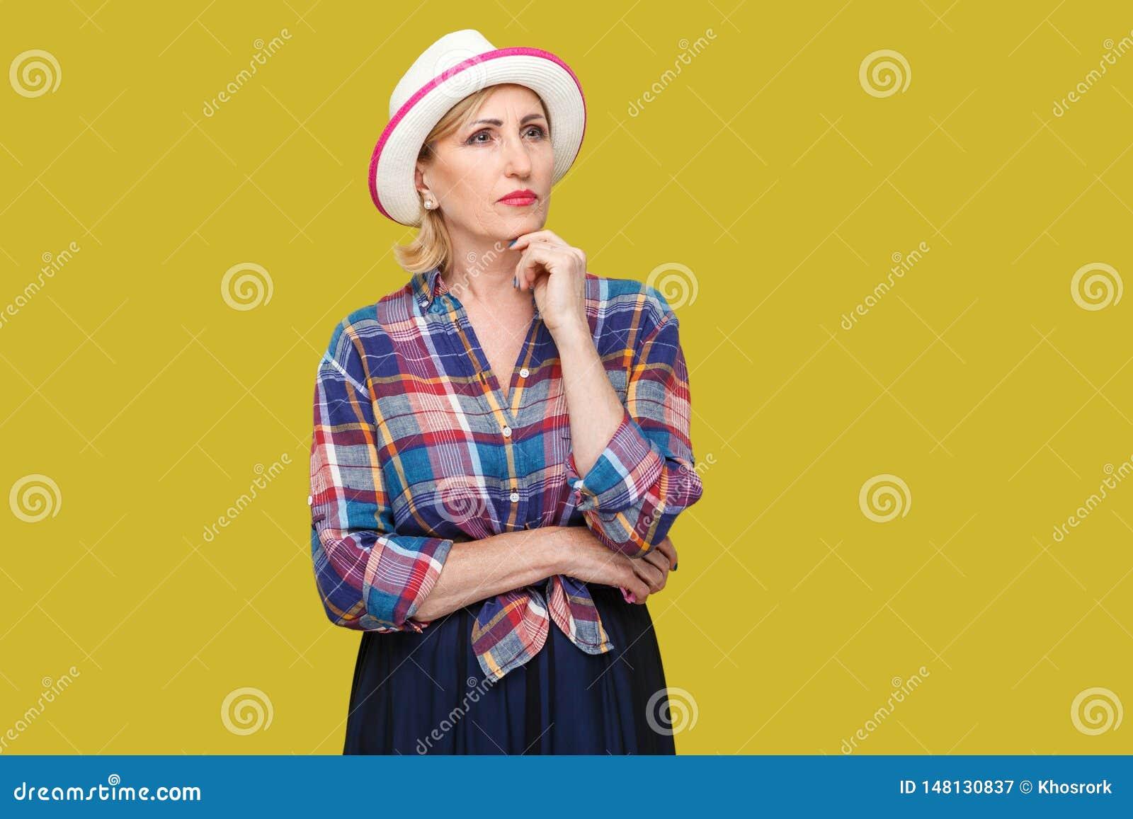 Retrato da mulher madura à moda moderna pensativa séria no estilo ocasional com posição branca do chapéu, tocando em seu queixo,