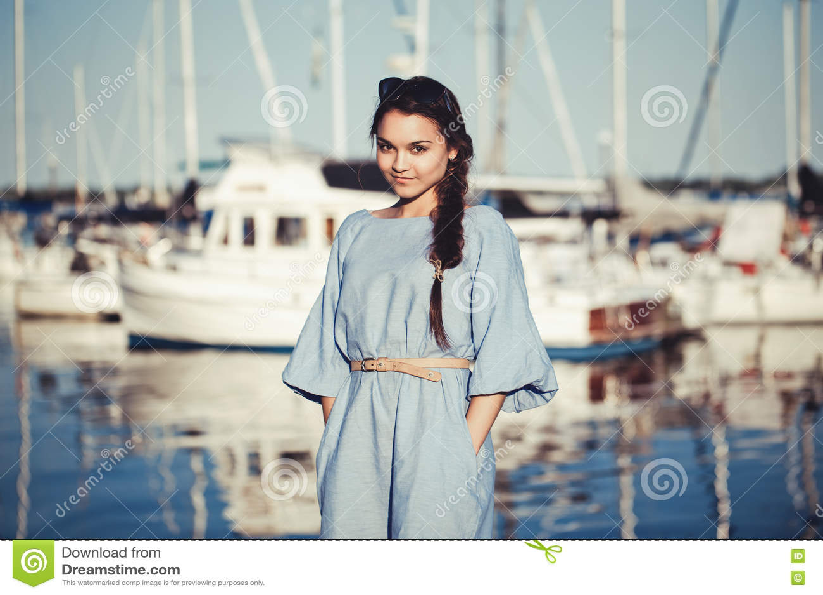 Retrato da mulher moreno caucasiano branca bonita com pele bronzeada no vestido azul, pelo litoral lakeshore