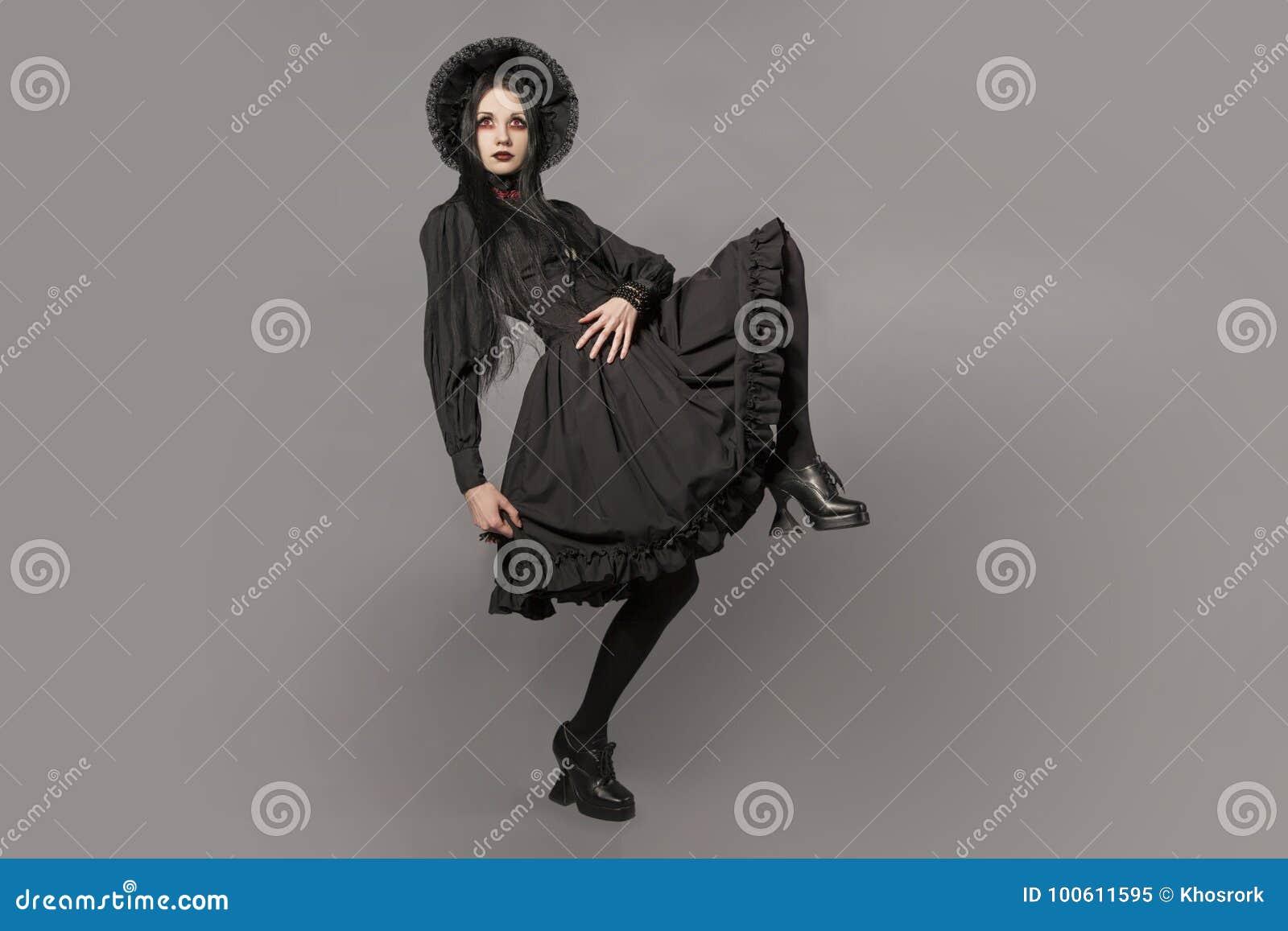 Retrato da mulher moreno no vestido preto e do estilo gótico clássico com  os olhos vermelhos no fundo cinzento Conceito de Halloween 23845f6fa1