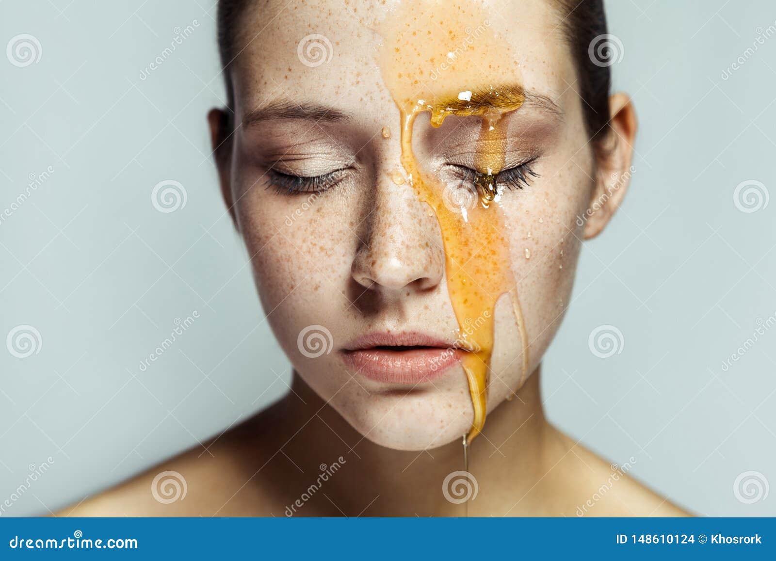 Retrato da mulher moreno nova bonita com sardas e mel na cara com olhos fechados e a cara s?ria