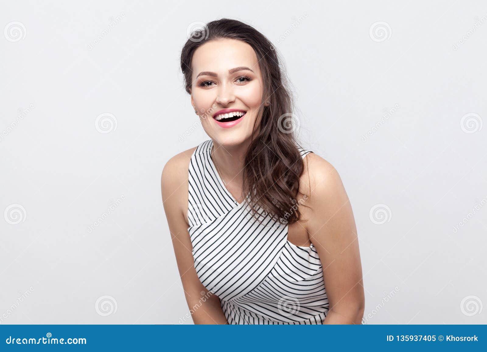 Retrato da mulher moreno nova bonita feliz com composição e posição listrada do vestido e vista da câmera com sorriso toothy