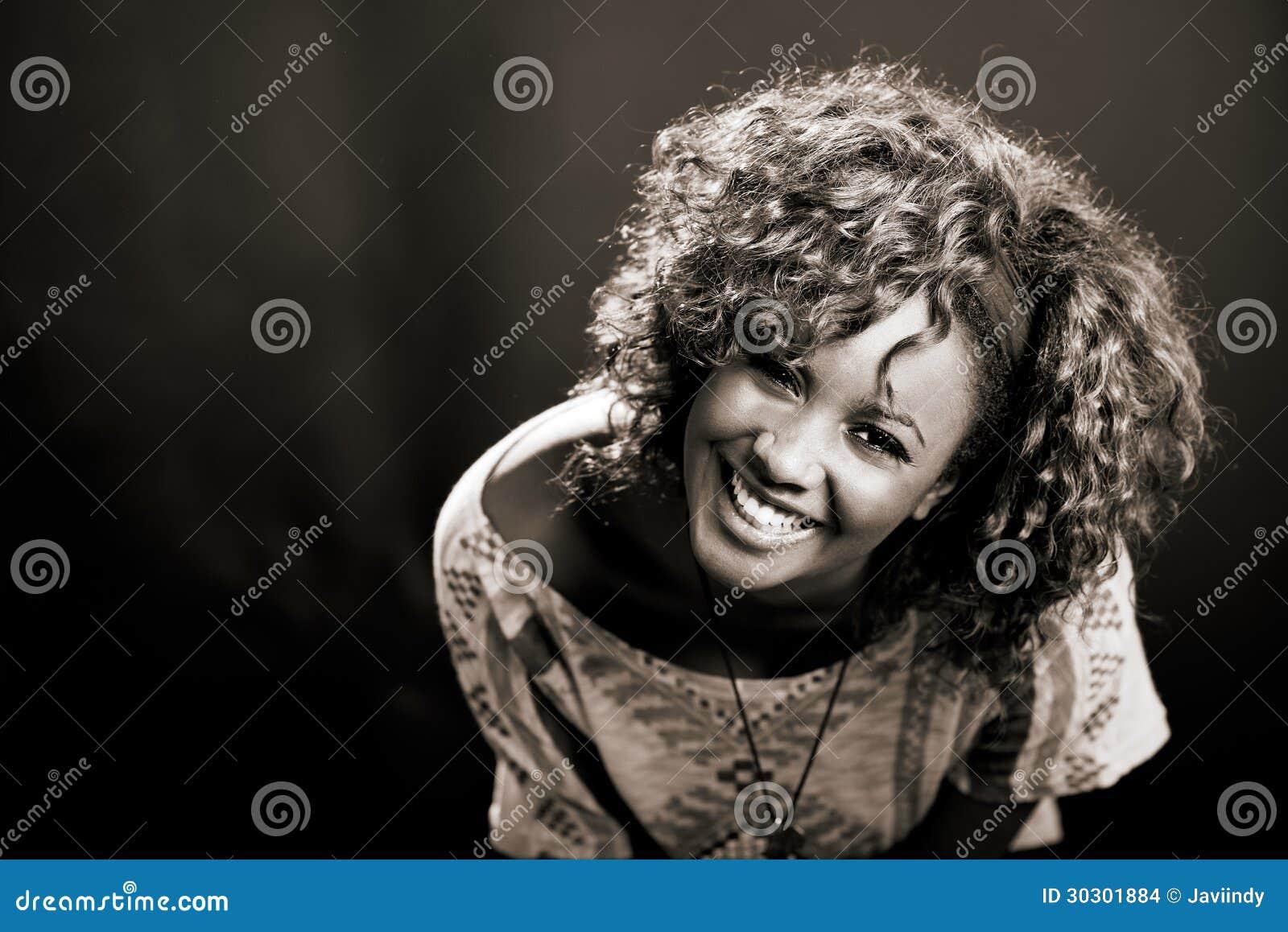 Mulher negra bonita no fundo preto. Tiro do estúdio