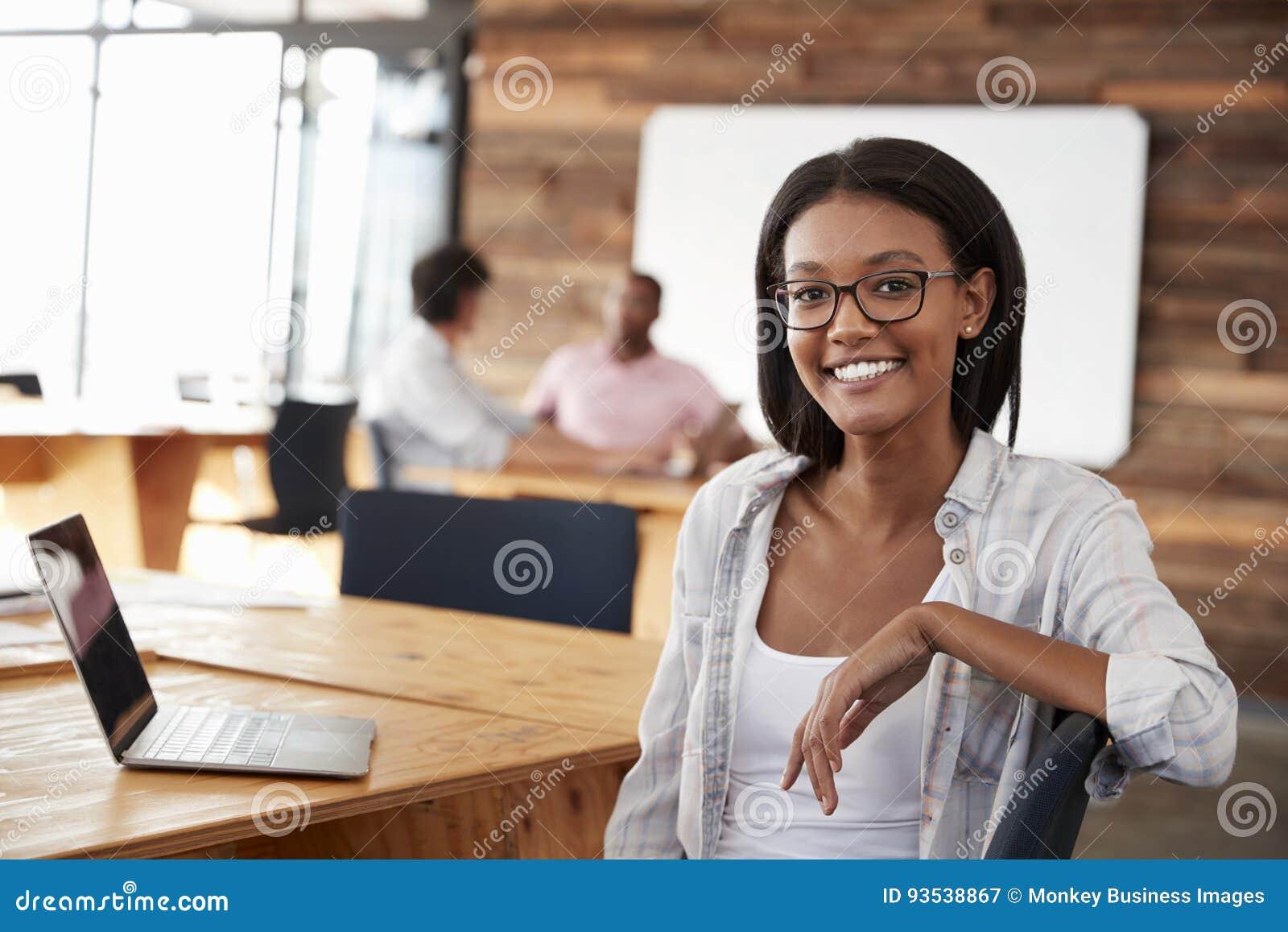 Retrato da mulher negra nova no escritório criativo