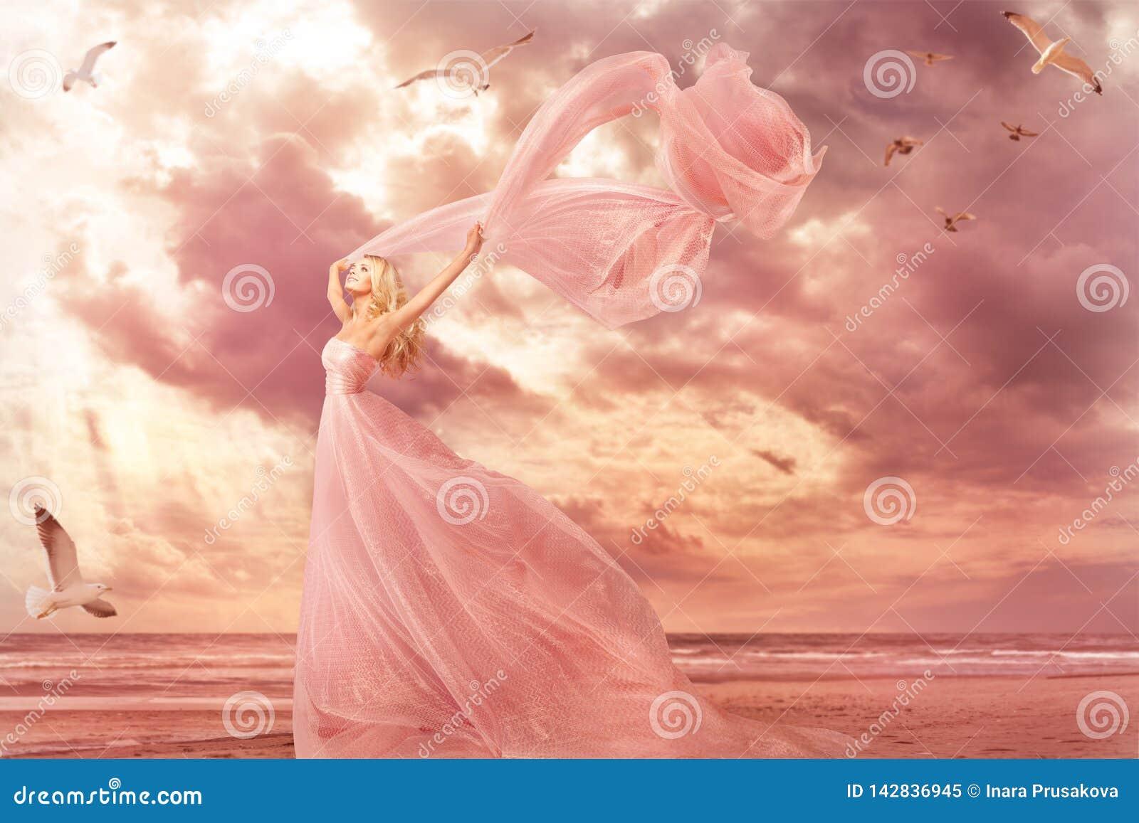 Retrato da mulher no vestido longo na costa de mar, vestido do rosa da menina da fantasia no vento de tempestade