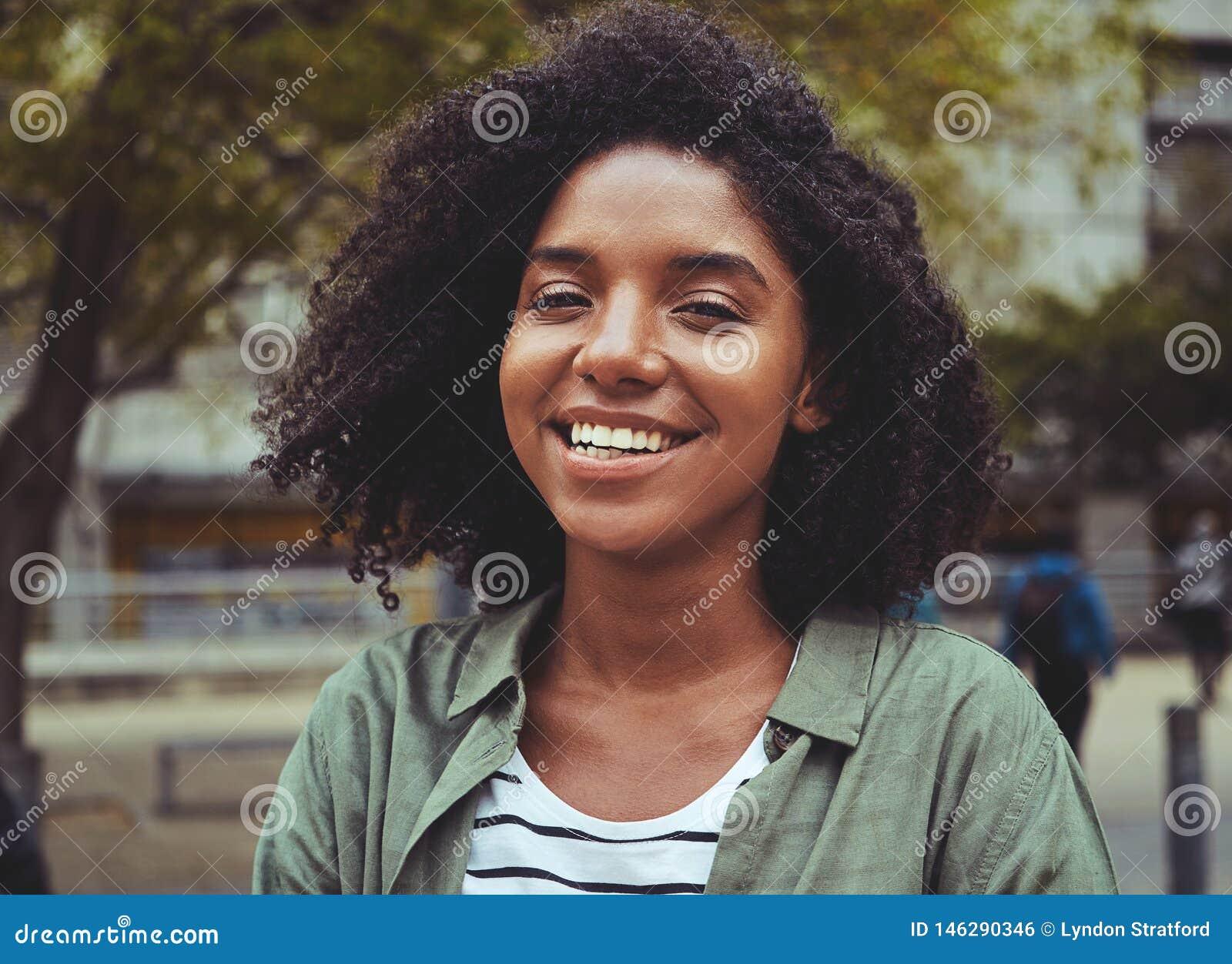 Retrato da mulher nova de sorriso ao ar livre