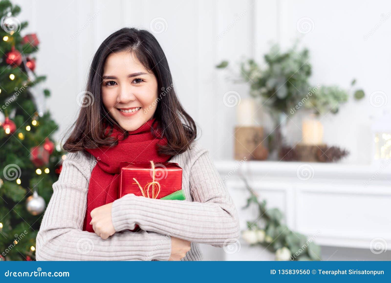 Retrato da mulher ou do adolescente asiático novo atrativo que sorriem e que olham a câmera que guarda o presente vermelho do pre