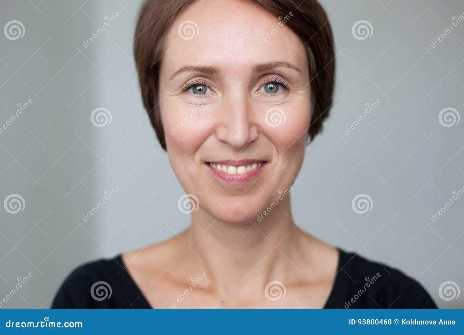 Retrato da mulher presumido no estilo da roupa ocasional Sorri amplamente