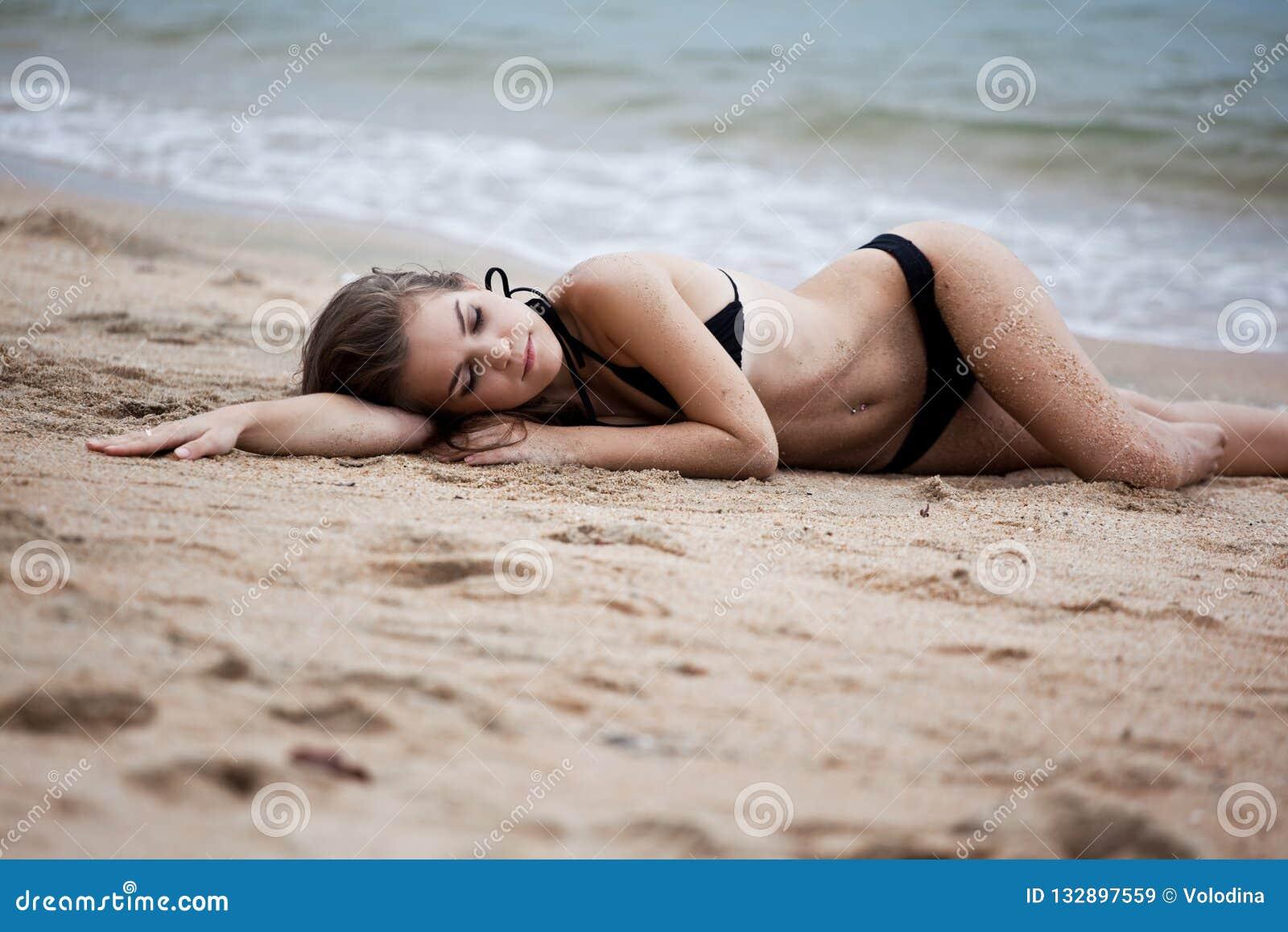 Retrato da mulher que encontra-se na praia da areia