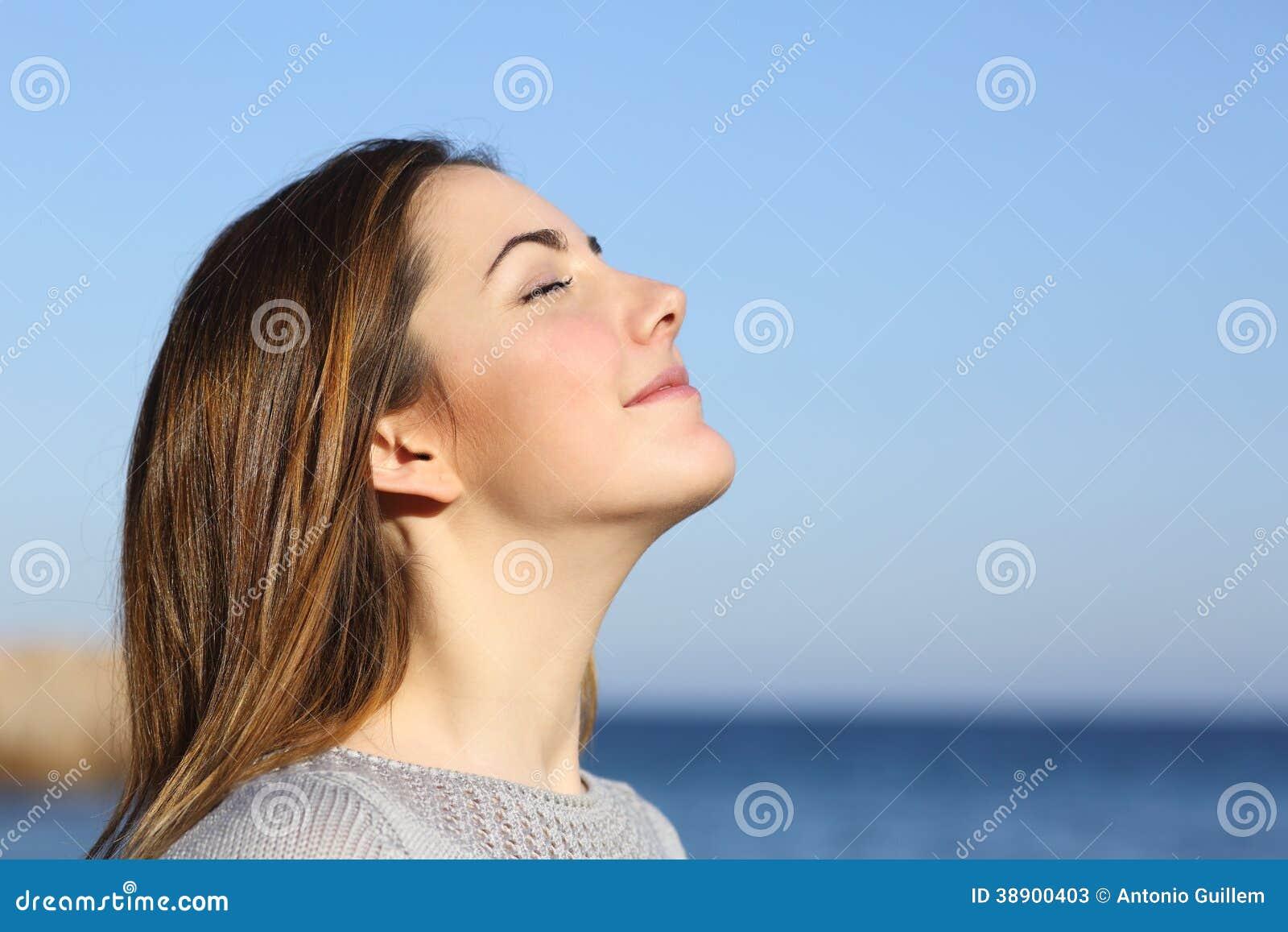 Retrato da mulher que respira o ar fresco profundo
