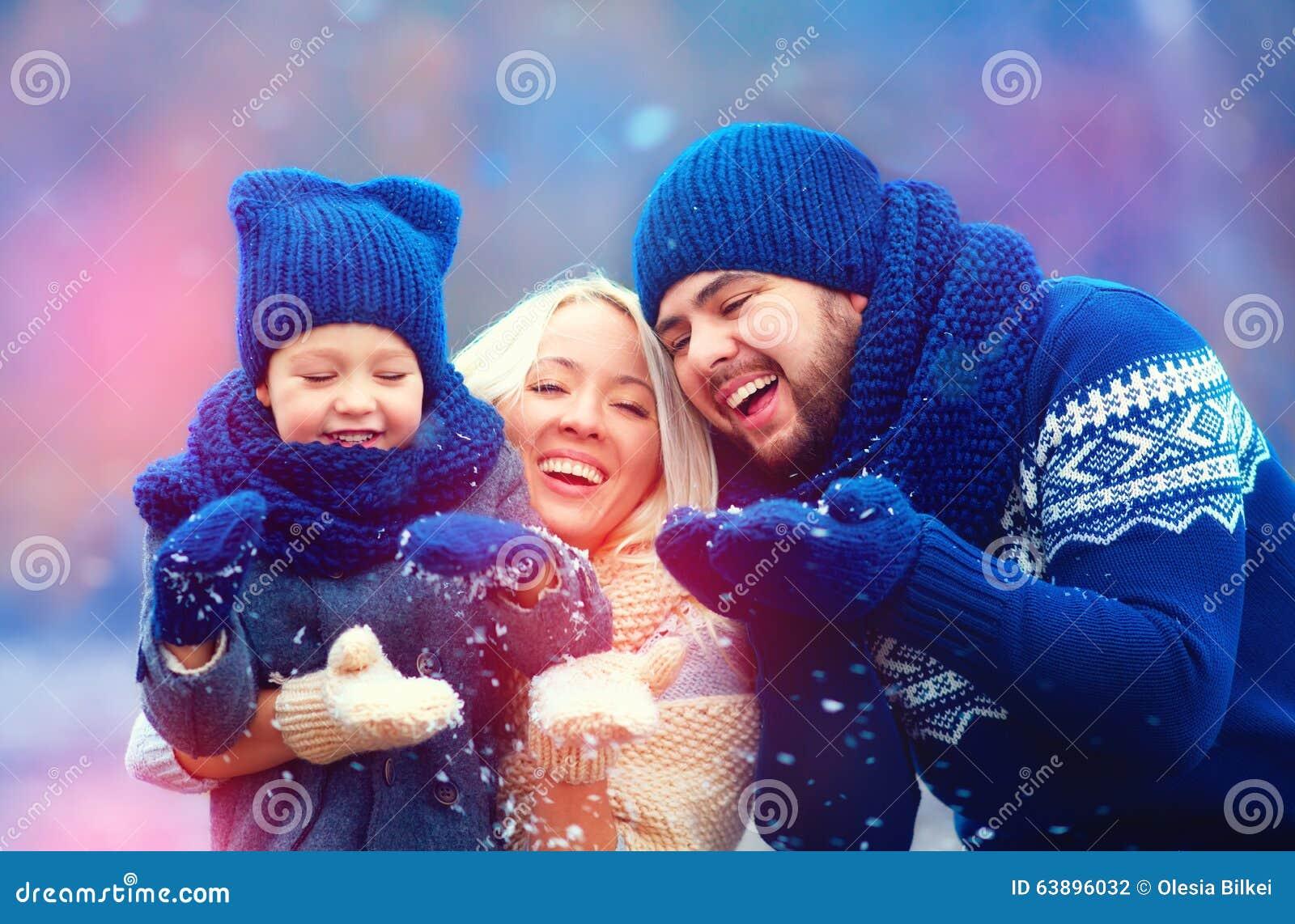 Retrato da neve de sopro do inverno da família feliz fora, época natalícia