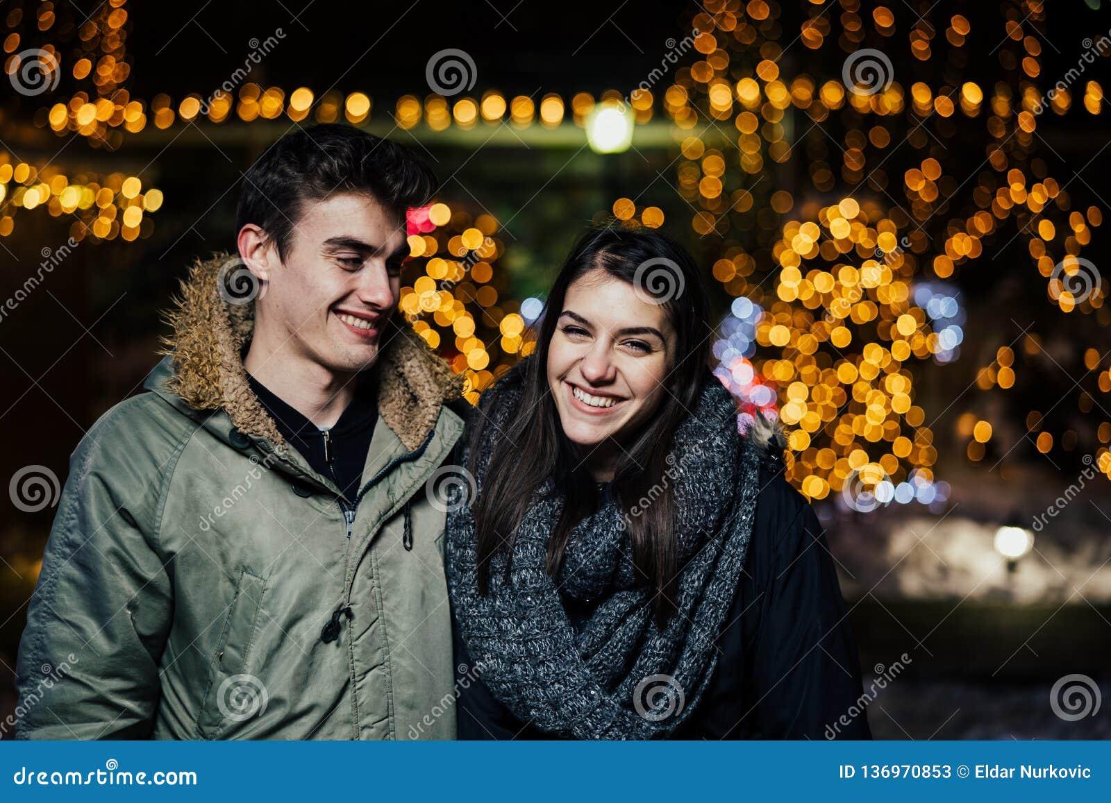 Retrato da noite de um par feliz que sorri apreciando aoutdoors do inverno e da neve Alegria do inverno Emoções positivas felicid