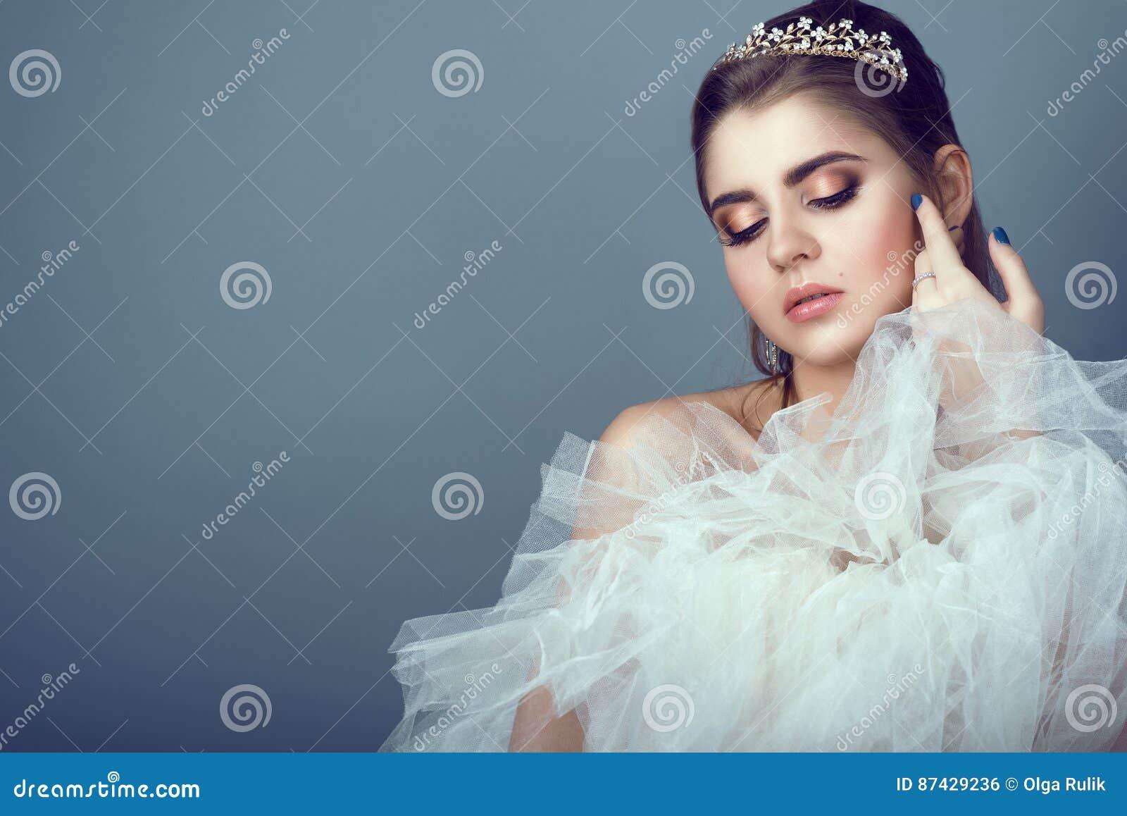 Retrato da noiva bonita nova no diadema que pressiona a saia macia de seu vestido de casamento a seu peito
