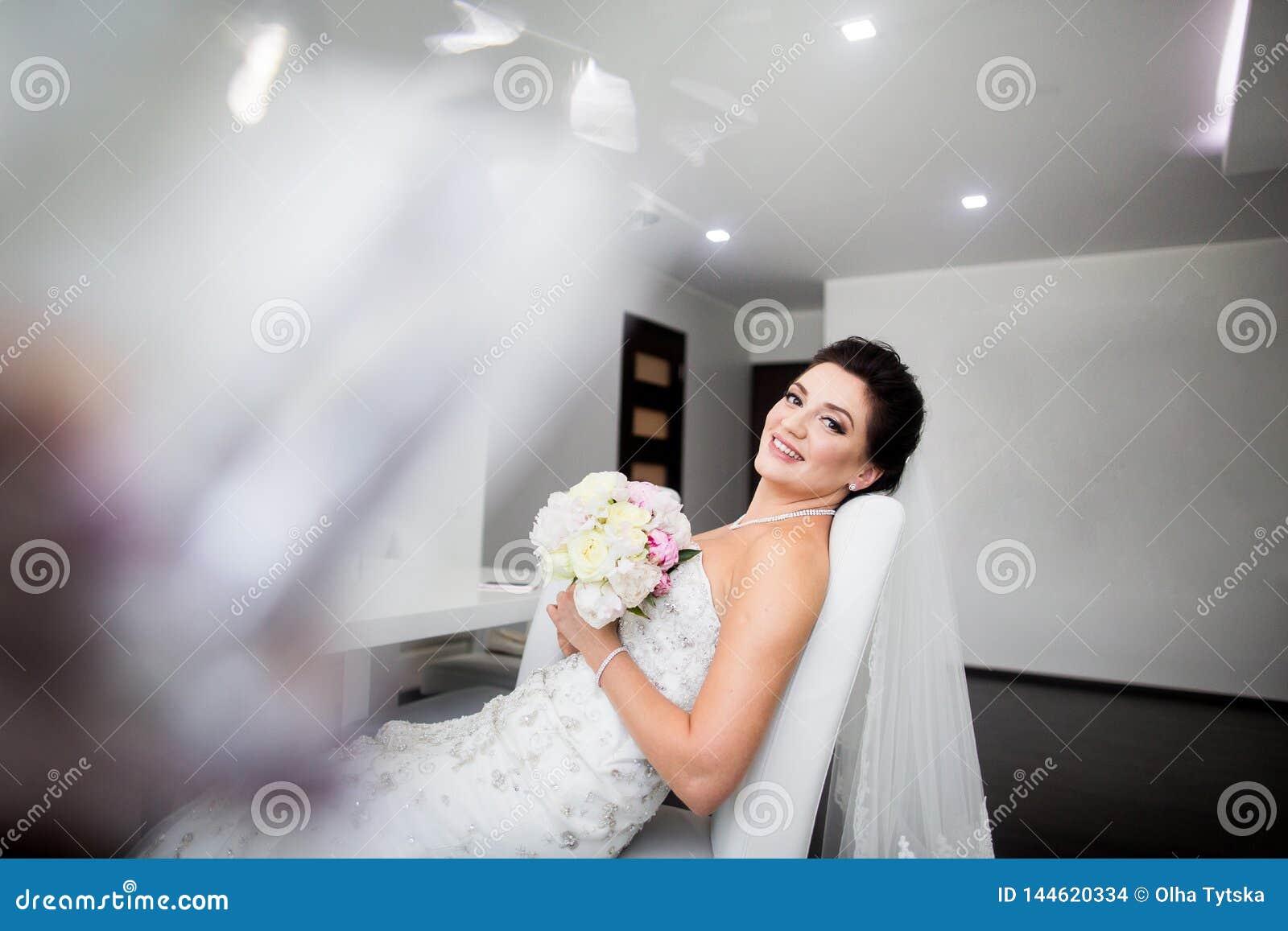 Retrato da noiva feliz bonita que senta-se no sof?