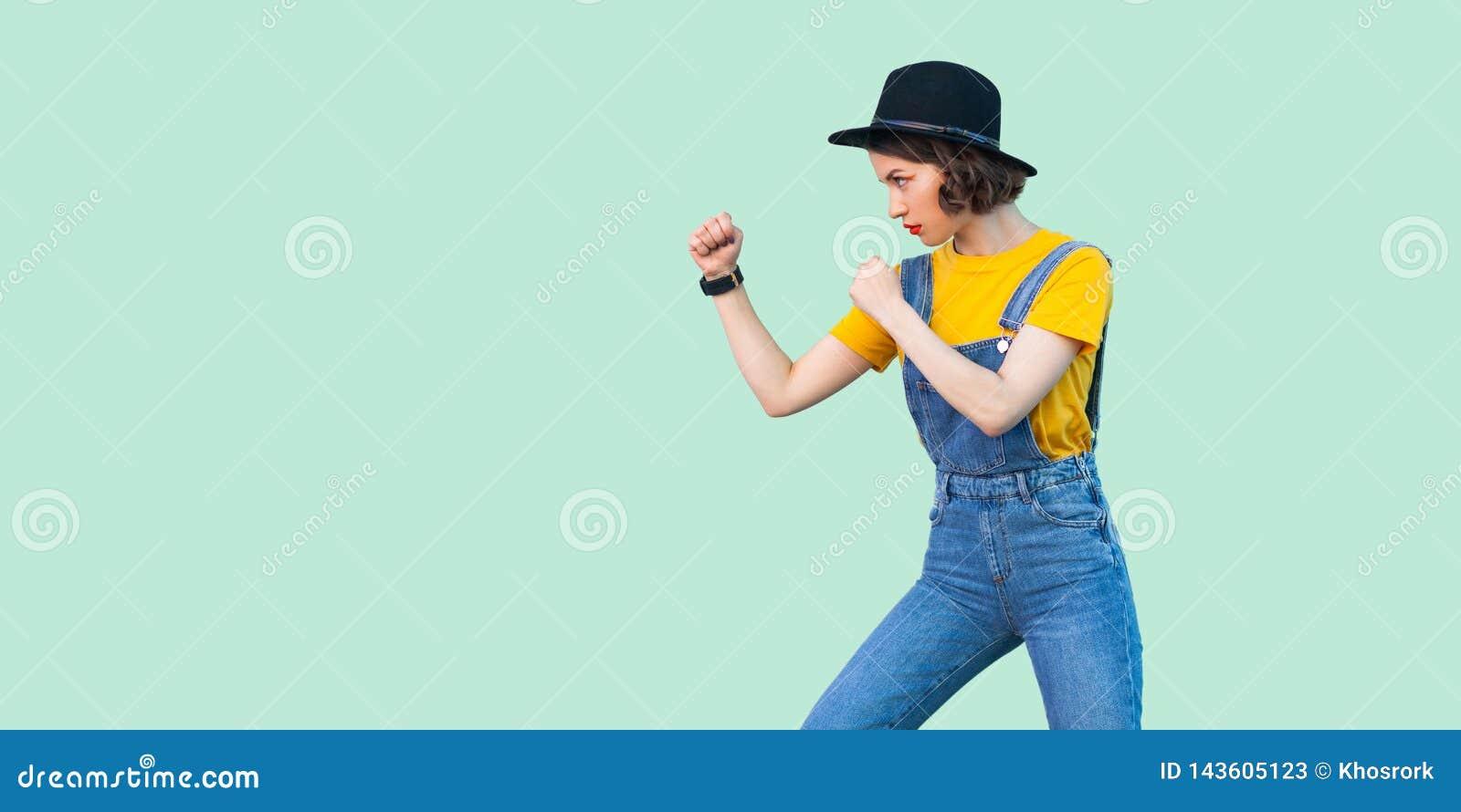 Retrato da opinião lateral do perfil da moça séria em macacões azuis da sarja de Nimes, camisa amarela, posição do chapéu negro c