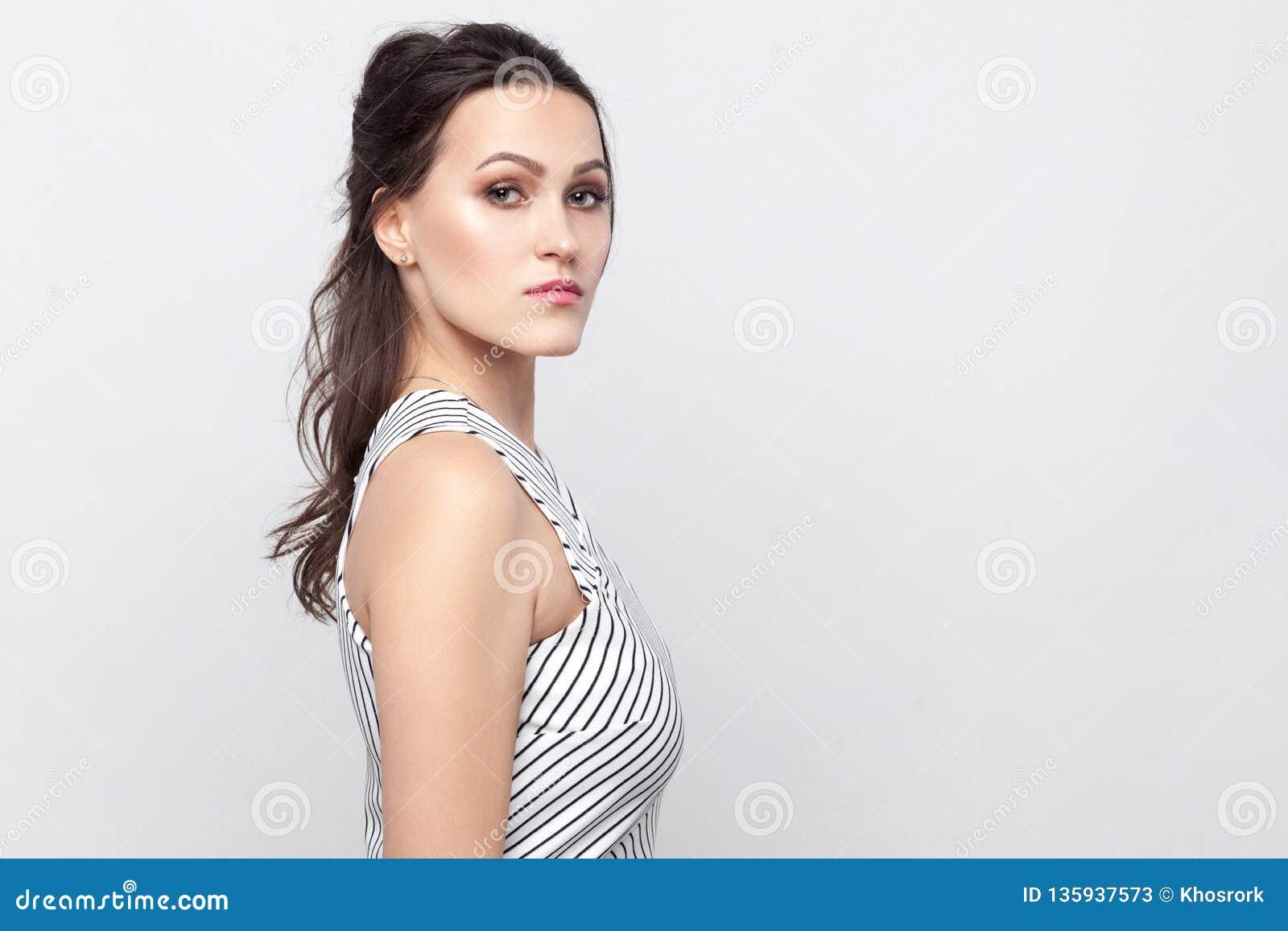 Retrato da opinião lateral do perfil da mulher moreno nova bonita séria com composição e posição listrada do vestido e vista da c