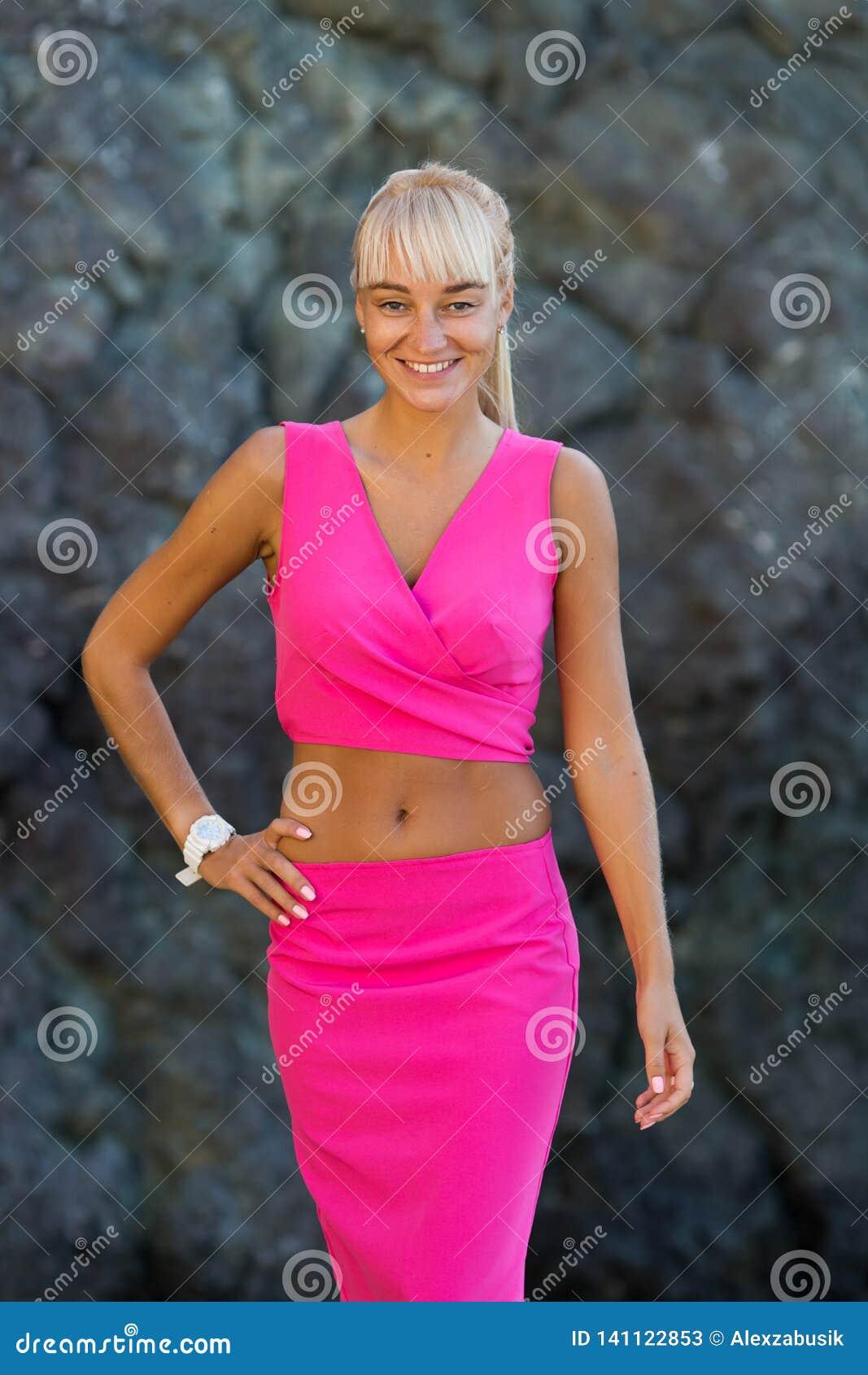 Retrato da pessoa fêmea atrativa no terno cor-de-rosa