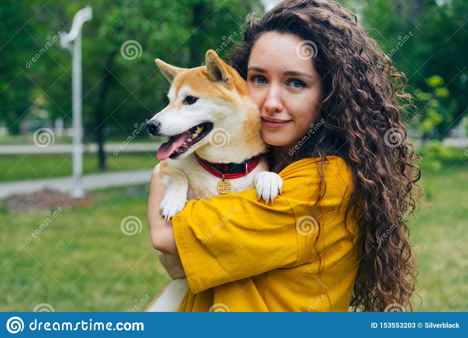 Retrato da posição de amor do proprietário do cão da menina bonita no parque com seu sorriso bonito do animal de estimação