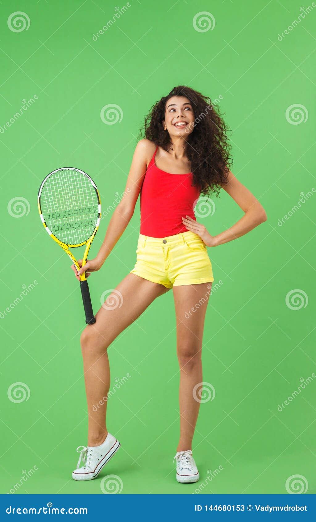 Retrato da raquete atrativa da terra arrendada da mulher e do tênis do jogo ao estar contra a parede verde