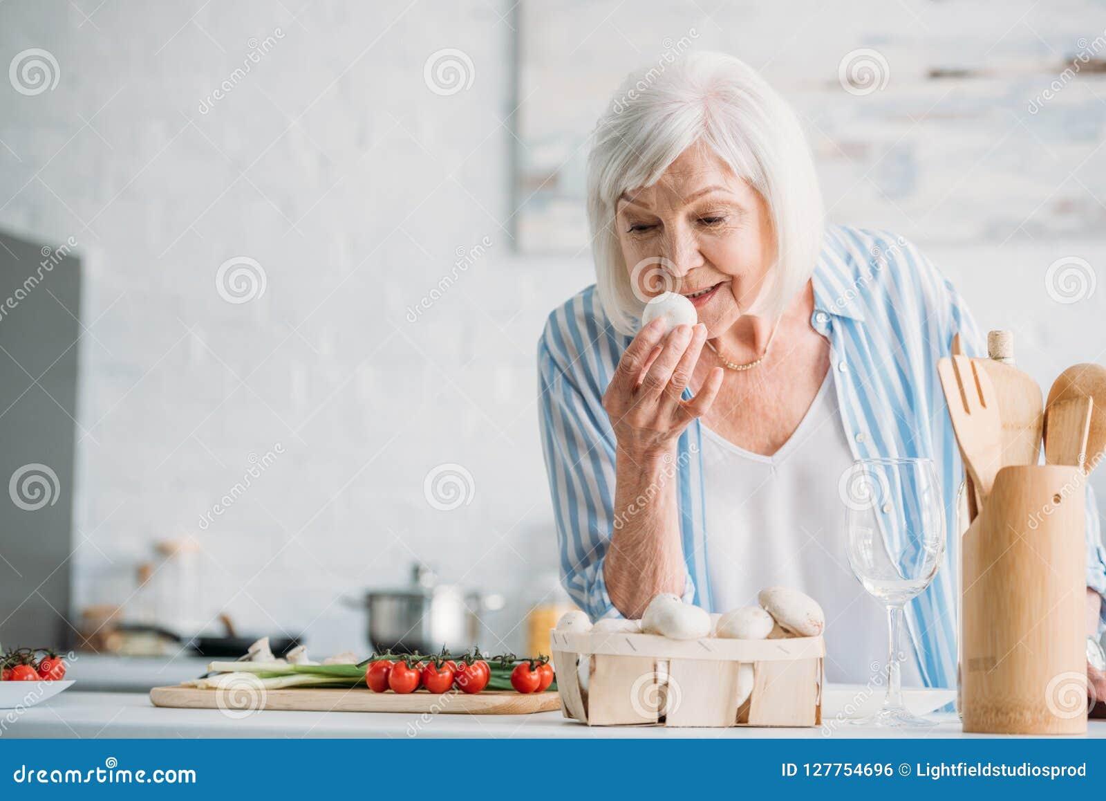 Retrato da senhora cinzenta do cabelo que verifica cogumelos ao cozinhar o jantar no contador