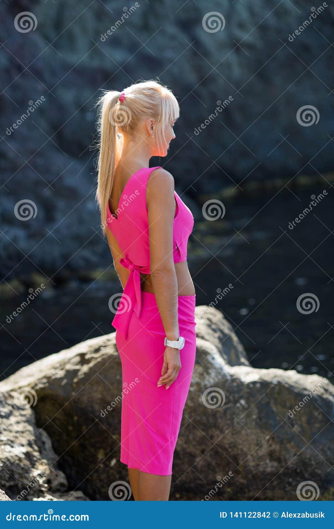Retrato da vista lateral da mulher na parte superior cor-de-rosa e da saia contra o penhasco rochoso natural