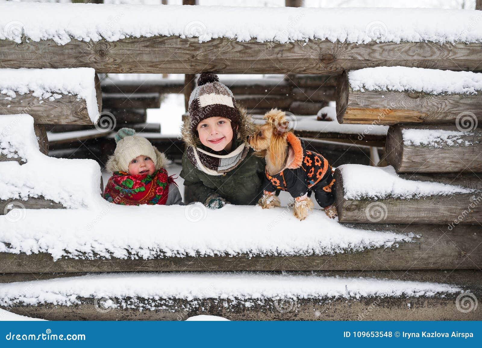 Retrato das crianças e do cão pequeno na perspectiva da casa coberto de neve inacabado na vila