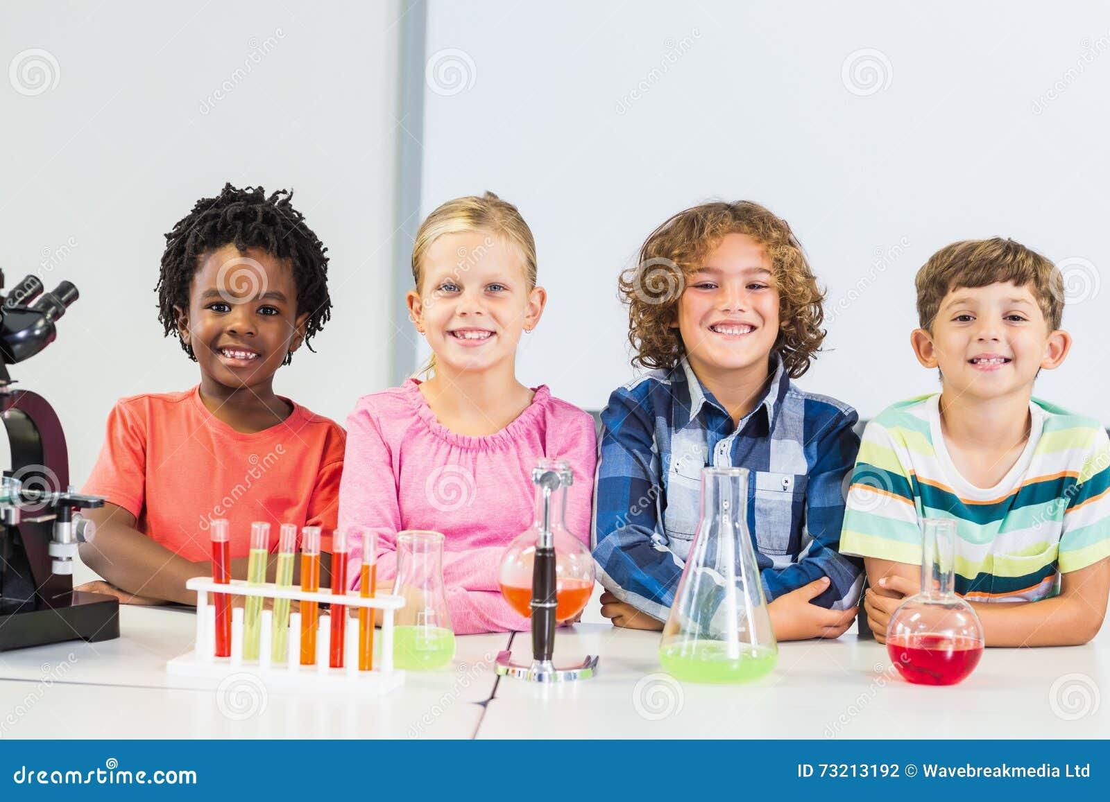 Retrato das crianças que fazem uma experiência química no laboratório