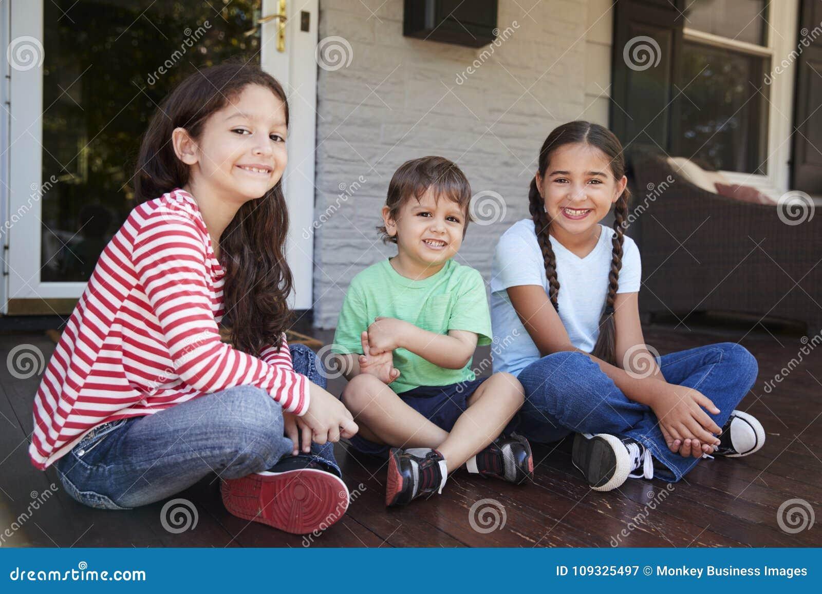 Retrato das crianças que sentam-se no patamar da casa junto