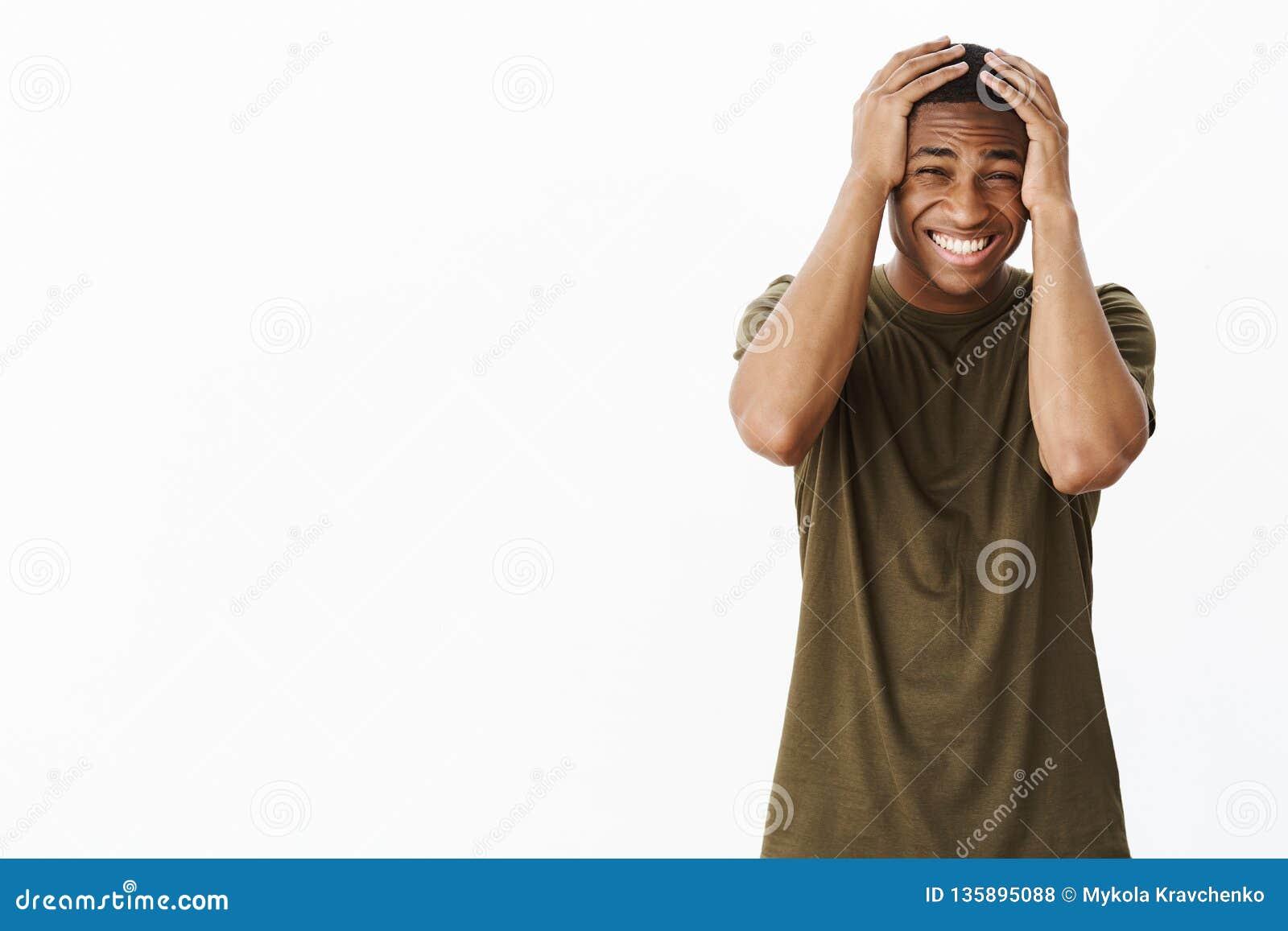 Retrato das mãos de pressão masculinas novas do afro-americano incomodado e interessado da virada nos dentes principais do clench