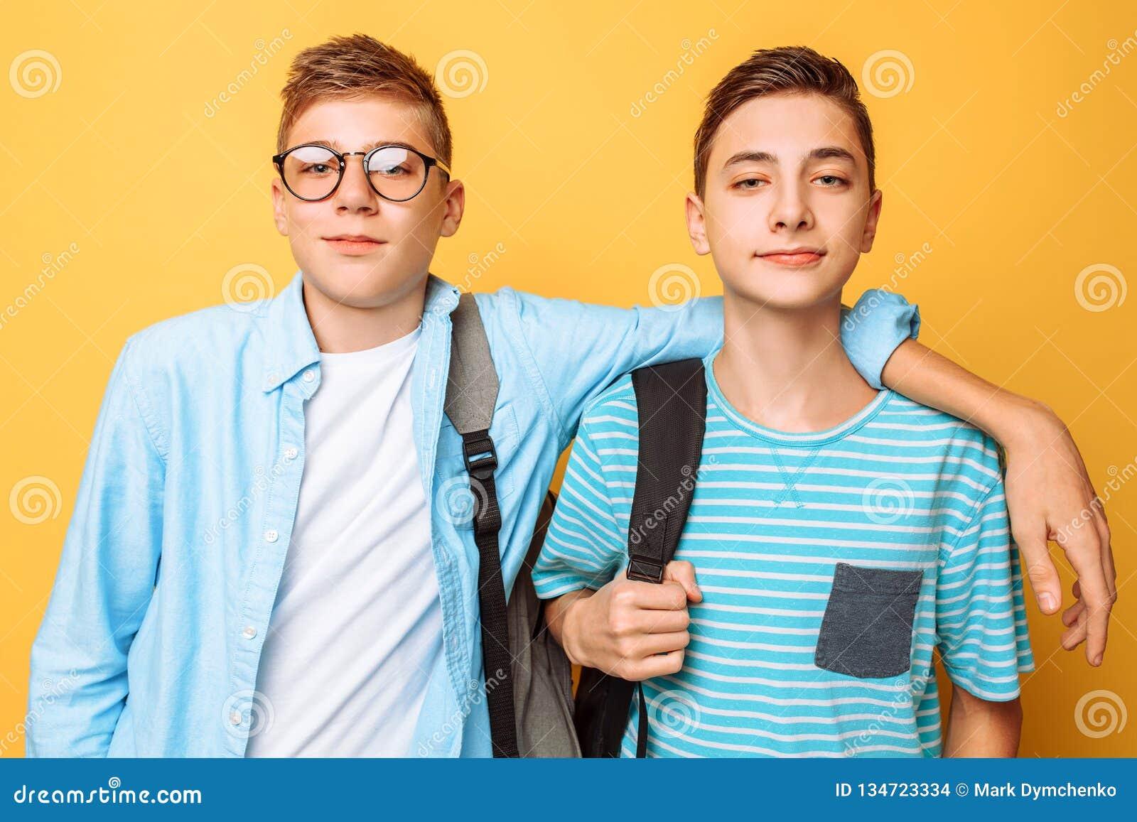 Retrato de dois indivíduos à moda felizes, adolescentes, isolados no fundo amarelo