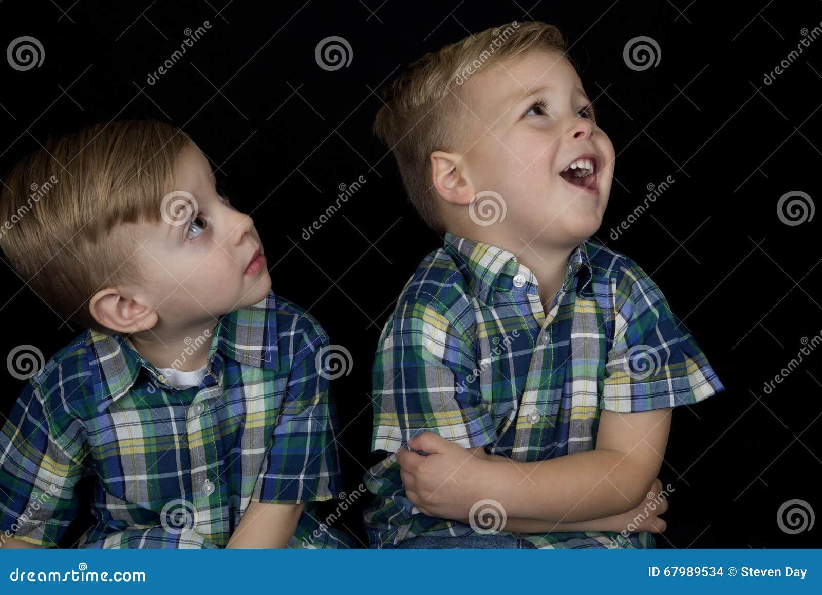 Retrato de dois meninos novos que combinam as camisas que olham acima longe de