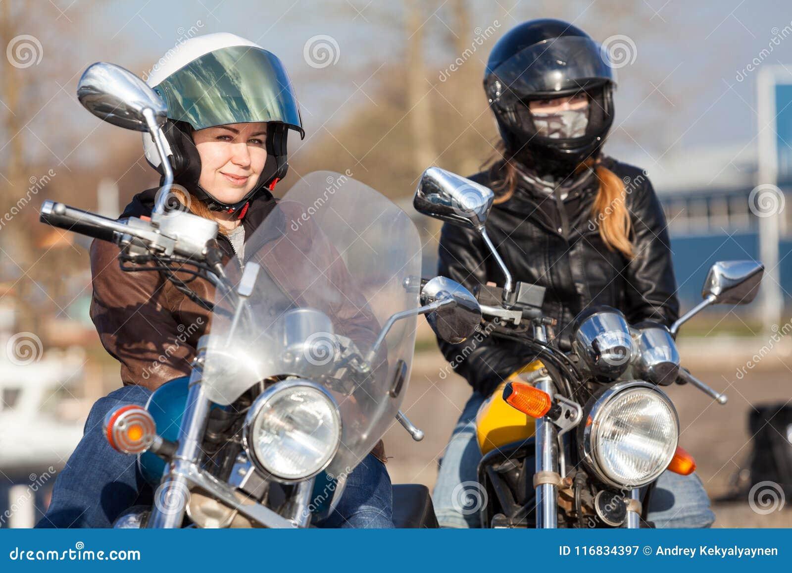 Retrato de dois motociclistas consideravelmente fêmeas do europeu com as bicicletas do estilo do clássico e da rua