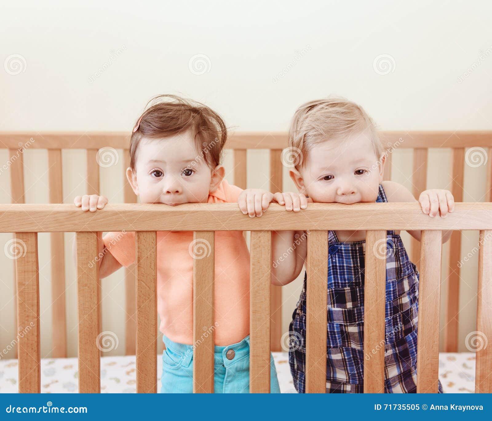 Retrato de dos amigos divertidos adorables lindos de los hermanos de los bebés de nueve meses que se colocan en pesebre de la cam