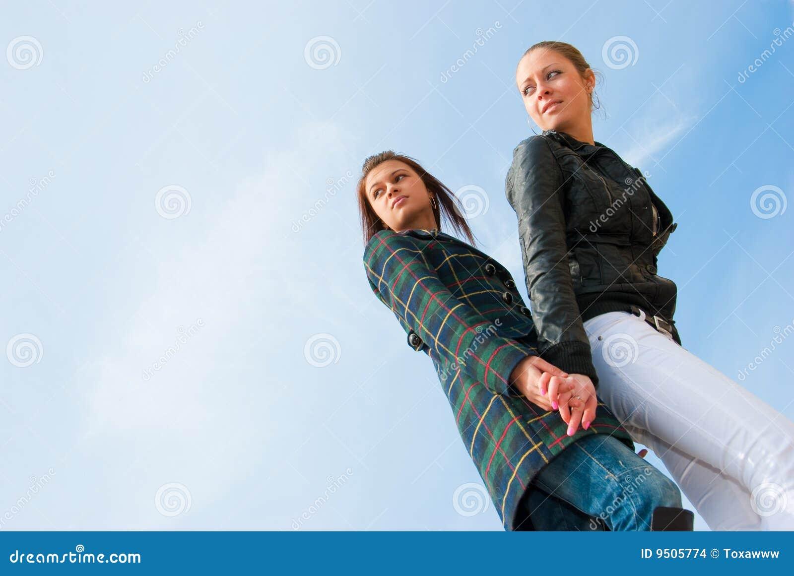 Retrato de dos chicas jóvenes sobre el cielo