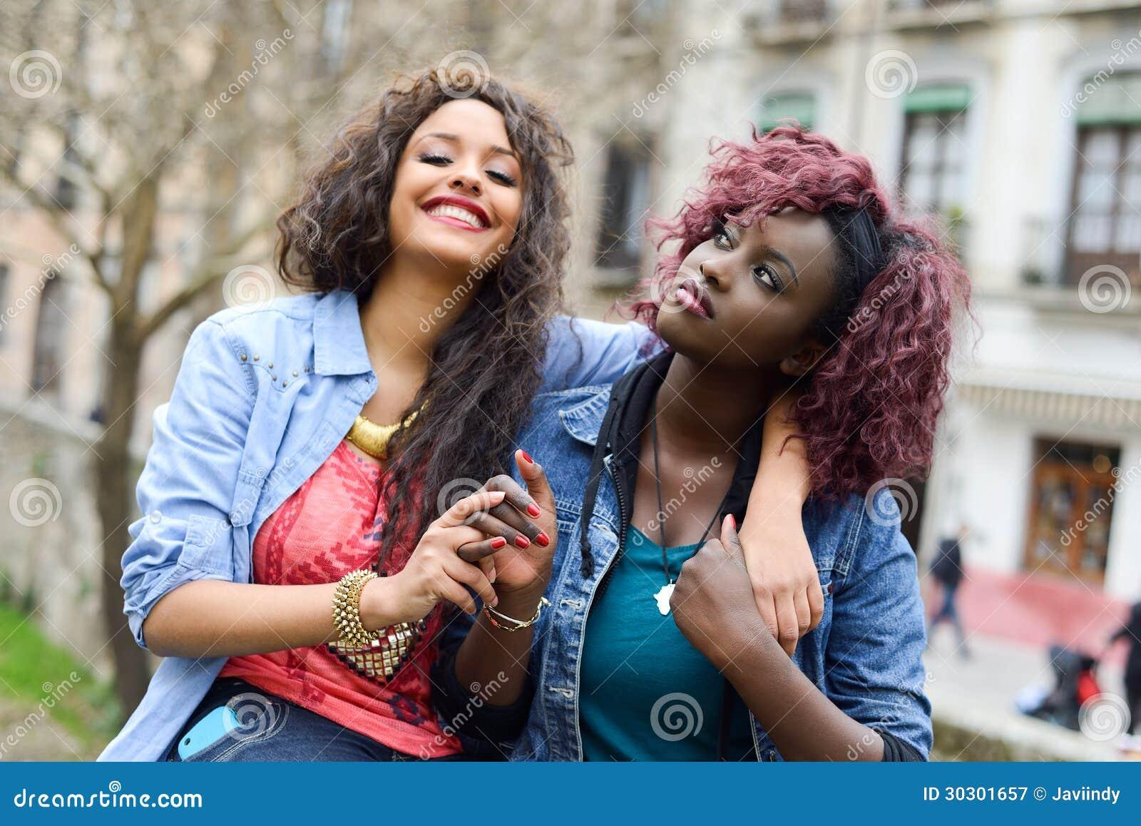 Dos muchachas hermosas en mujeres urbanas del backgrund, negras y mezcladas