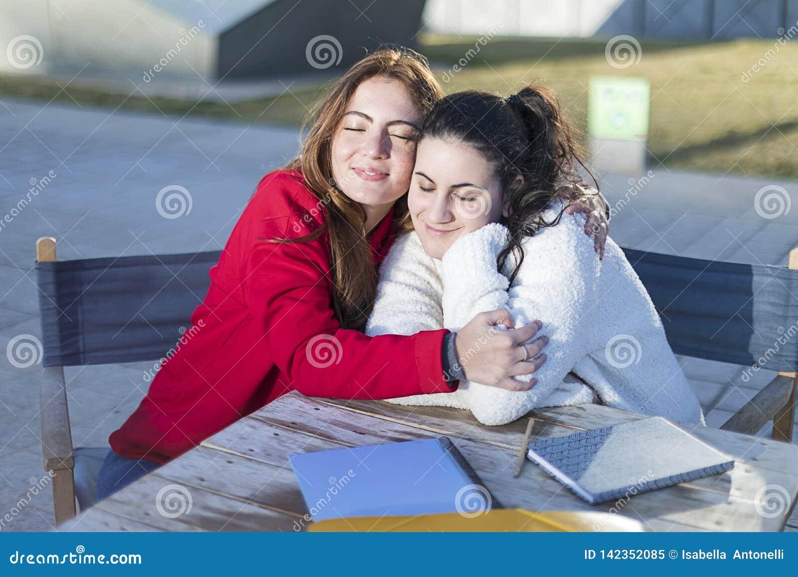 Retrato de duas jovens mulheres em um café exterior ao abraçar