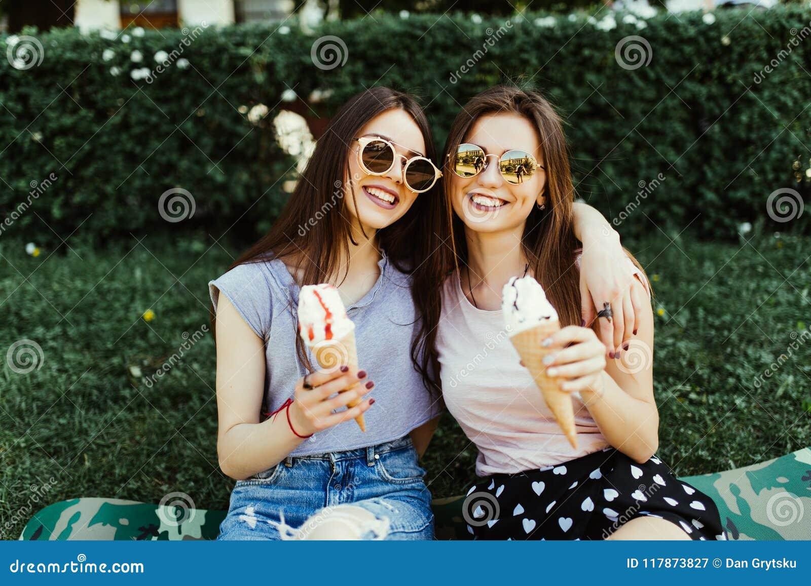 Retrato de duas jovens mulheres que estão junto comendo o gelado que abraça o assento na grama na rua da cidade