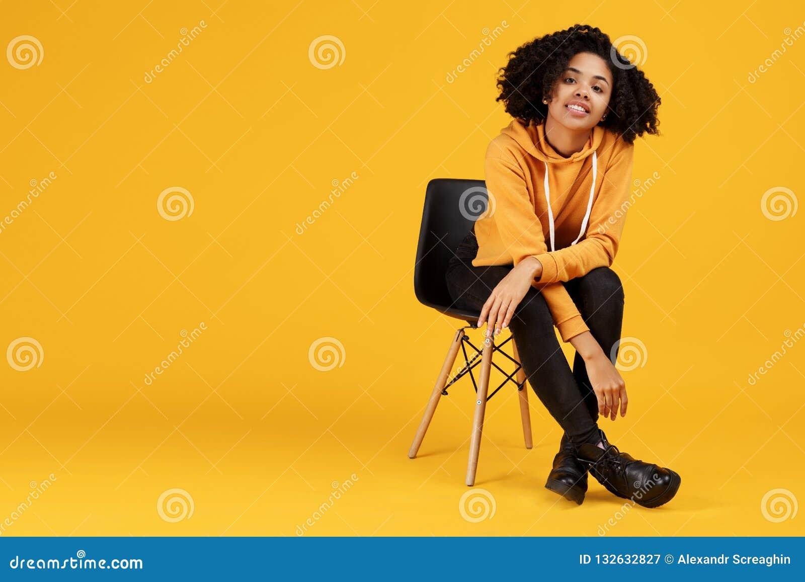 Retrato de encantar a jovem mulher afro-americano com sorriso bonito vestida na roupa ocasional que senta-se no à moda