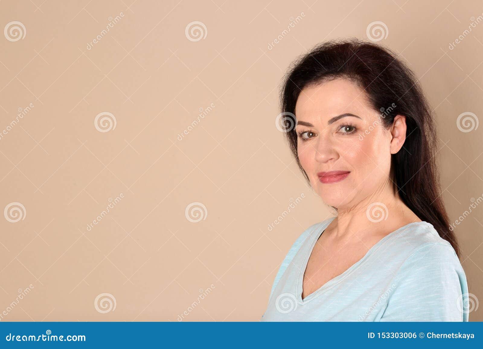 Retrato de encantar la mujer madura con la piel hermosa sana de la cara y el maquillaje natural en fondo beige