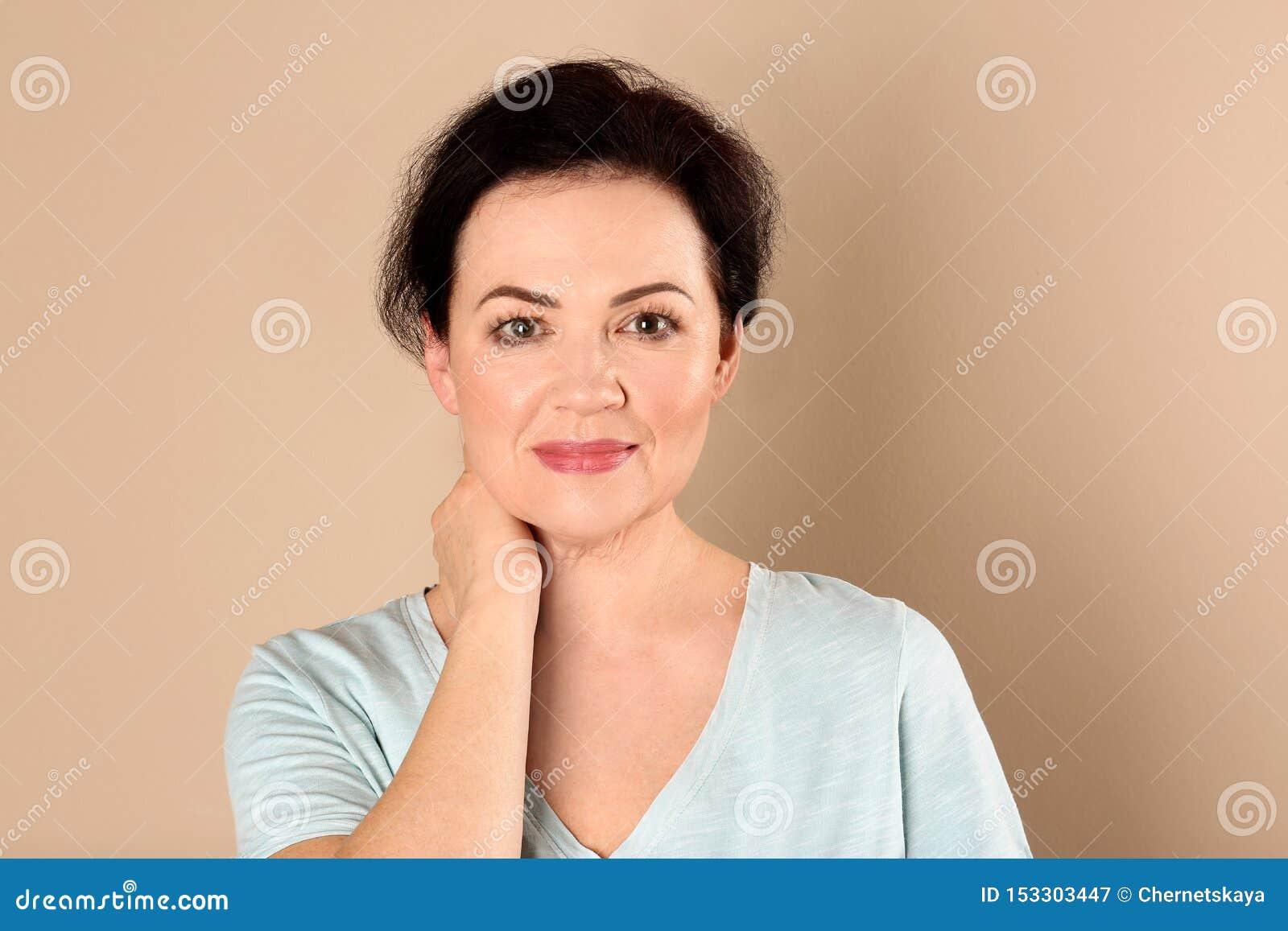Retrato de encantar la mujer madura con la piel sana de la cara y el maquillaje natural en fondo beige