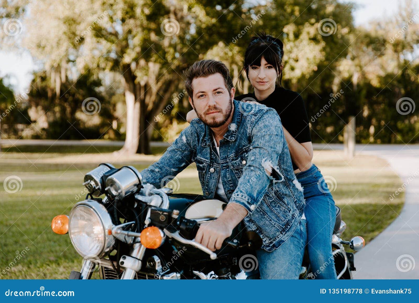 Retrato de Guy Girl Couple Riding de moda de moda moderno joven apuesto atractivo en escuela vieja del crucero verde de la motoci