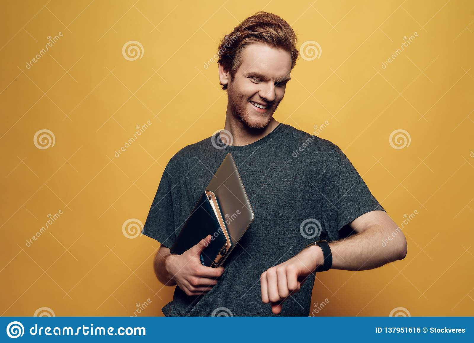 Retrato de Guy Holding Laptop joven alegre
