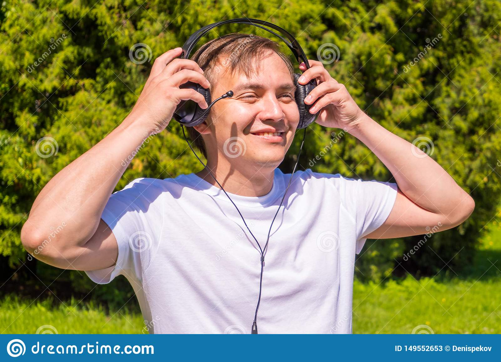 Retrato de hombres en auriculares, en la situaci?n blanca de la camiseta exterior en parque