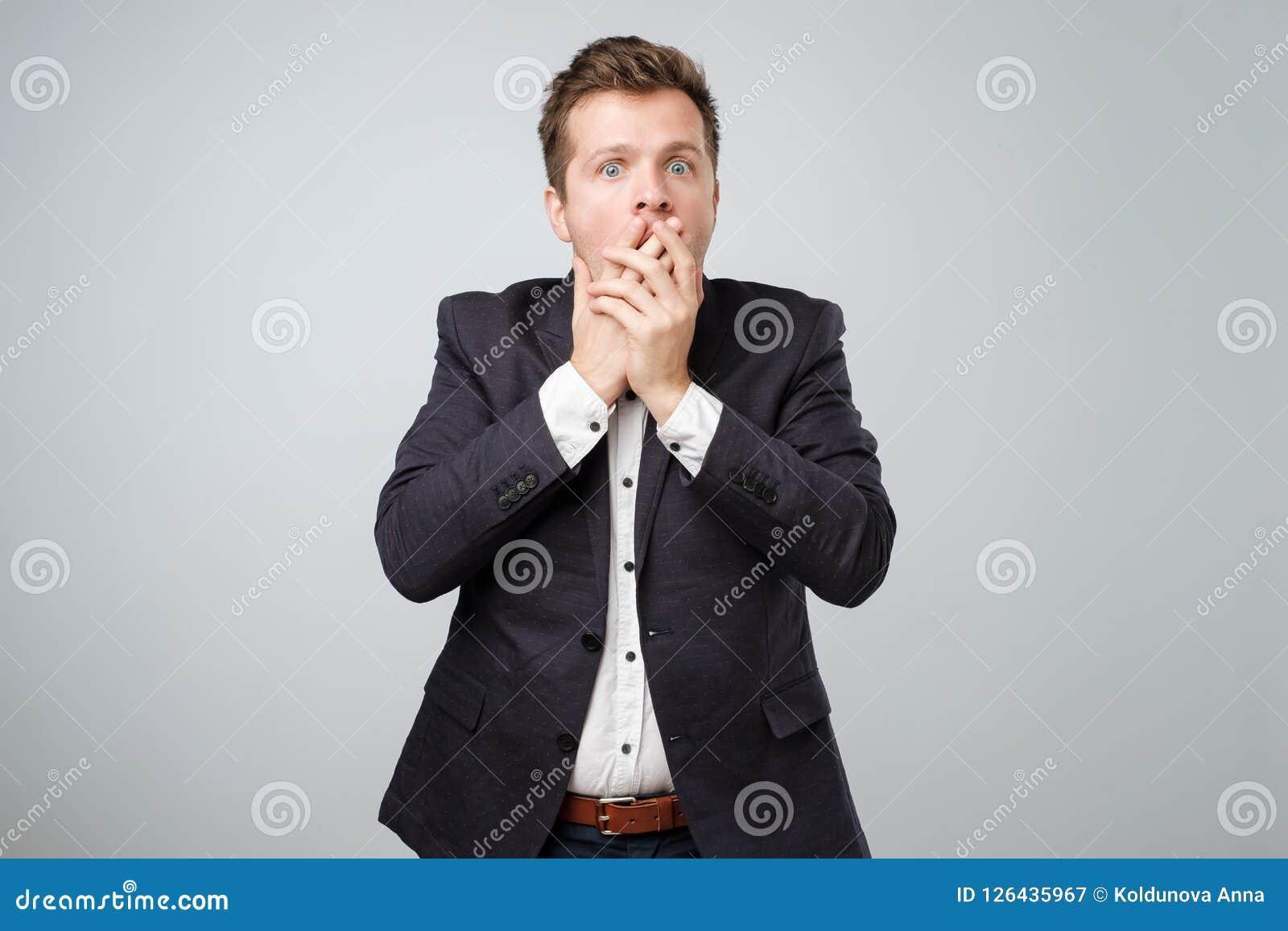 d67f6b2fa5b Retrato del hombre joven sorprendido en el traje que cubre su boca a mano  mientras que se coloca aislado en la pared gris No puedo creer estas  noticias