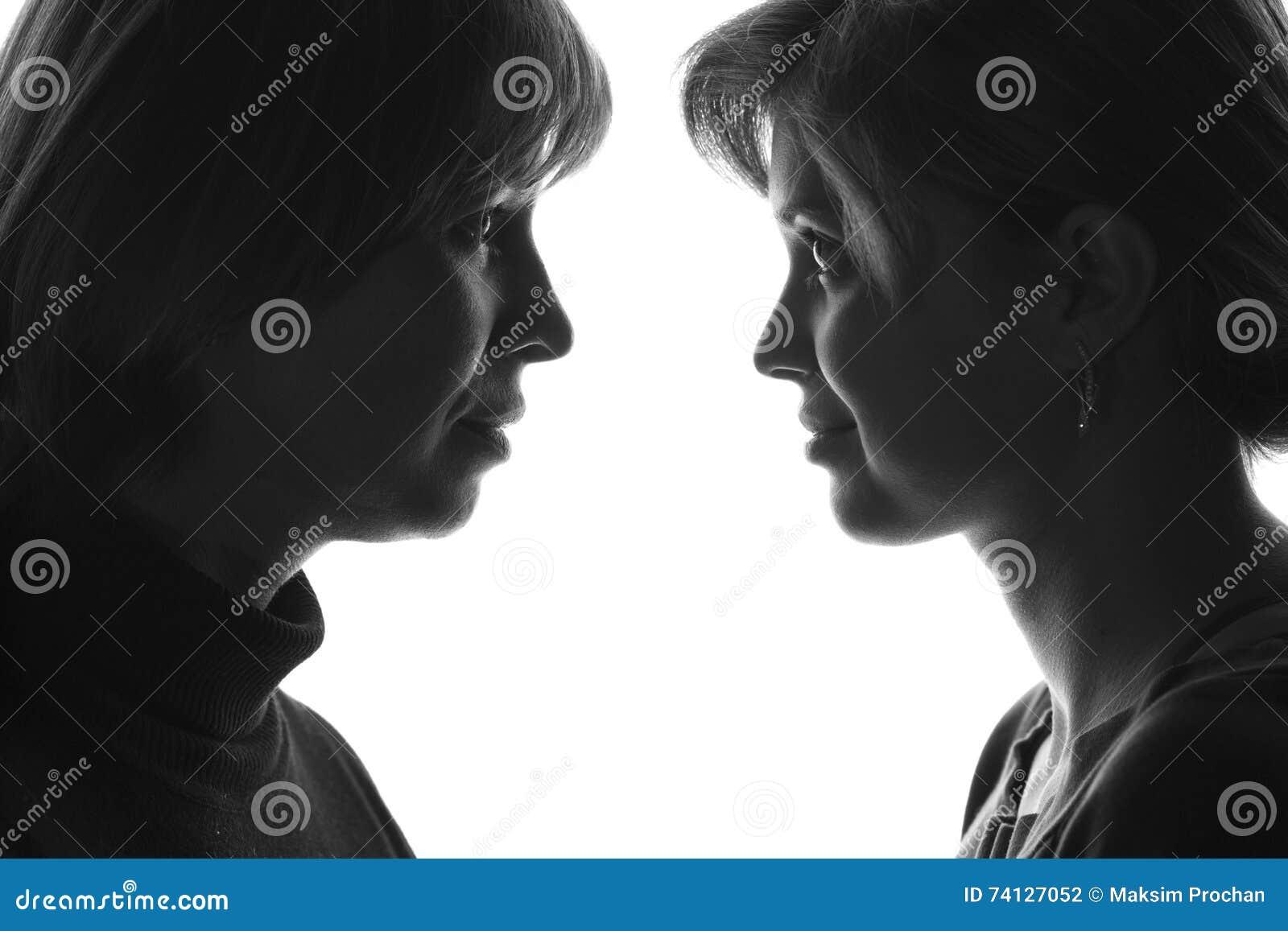 Retrato de la adolescencia de la madre y de la hija en el fondo aislado que mira uno a