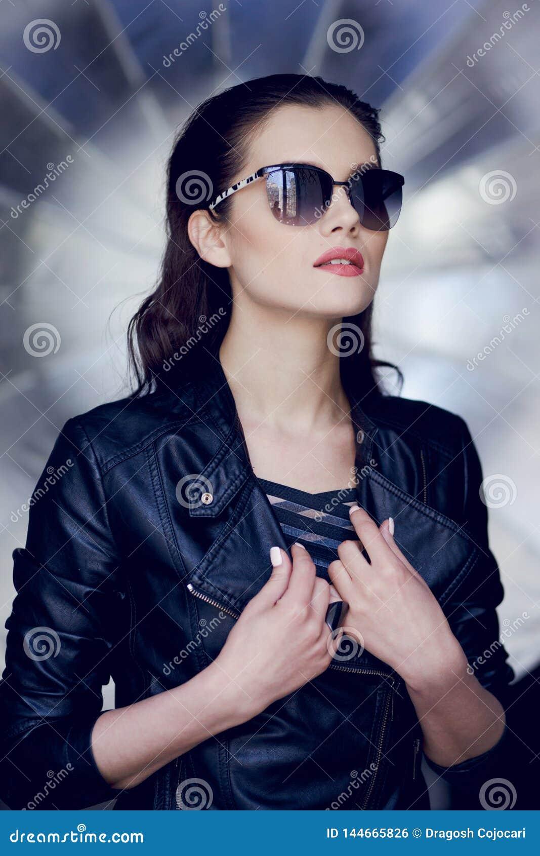 Retrato de la belleza de la mujer joven elegante en la chaqueta de cuero y las gafas de sol que miran lejos, aislado en un fondo