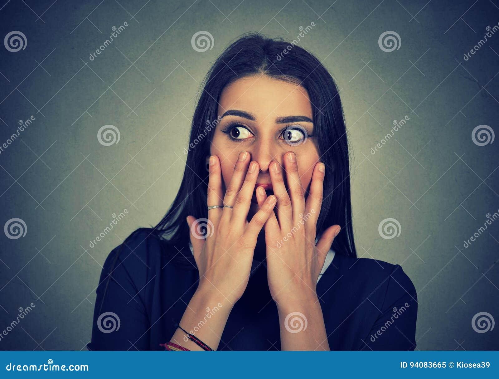 Retrato de la boca chocada sorprendida de la cubierta de la muchacha con las manos
