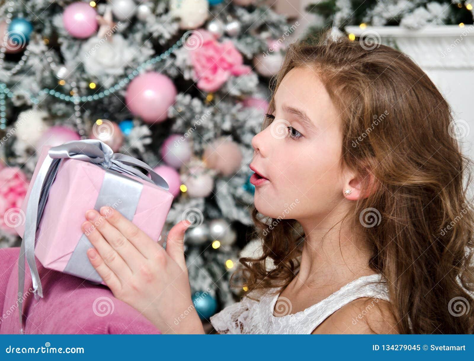 Retrato de la caja de regalo sorprendida feliz adorable de la tenencia del niño de la niña cerca del árbol de abeto