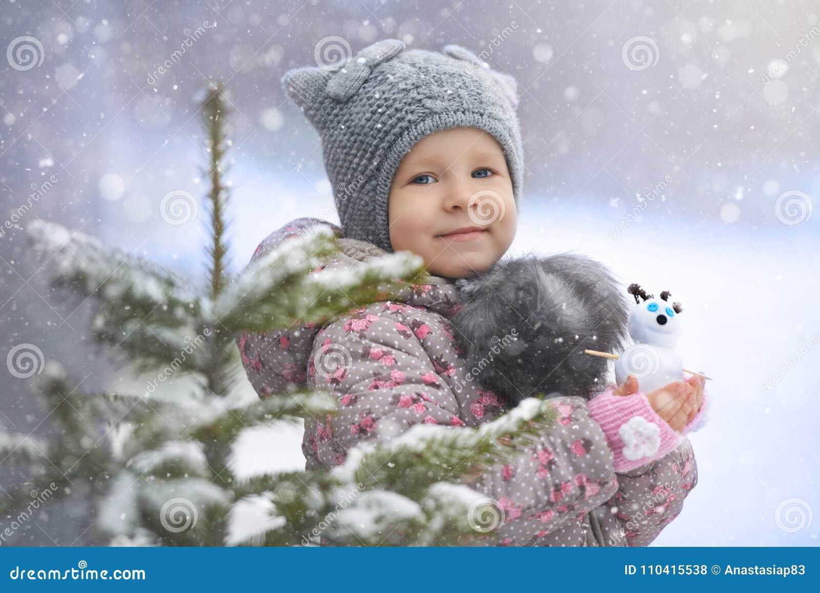 Retrato de la calle de la niña en el sombrero del gato con un muñeco de nieve que goza de la primera nieve