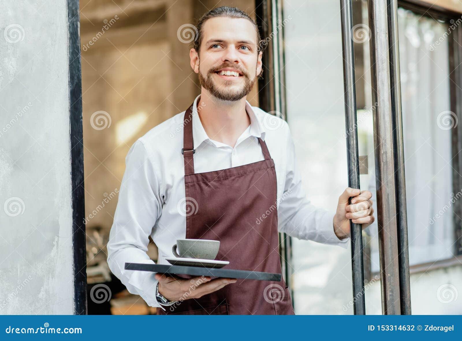 Retrato de la camarera de trabajo del hombre feliz barbudo del barista en puerta de entrada abierta del café y de bebidas de serv